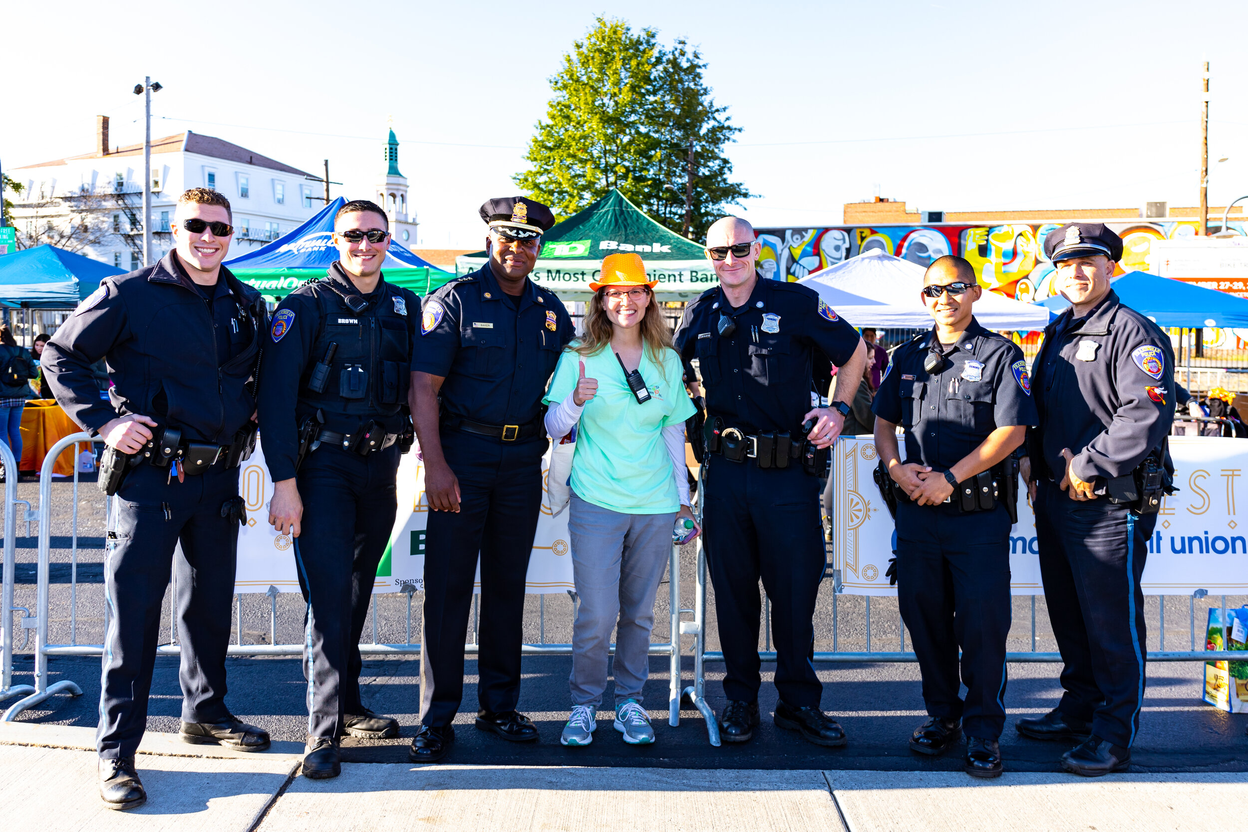 Framingham Police Department Deputy Chief Lester Baker (third from left), smiles as he leads his officers, including Downtown Beat Officer, Paul Dunkin (far right), at the Downtown Oktoberfest on October 5, organized by Downtown Framingham, Inc.'s Executive Director, Courtney Thraen (center).