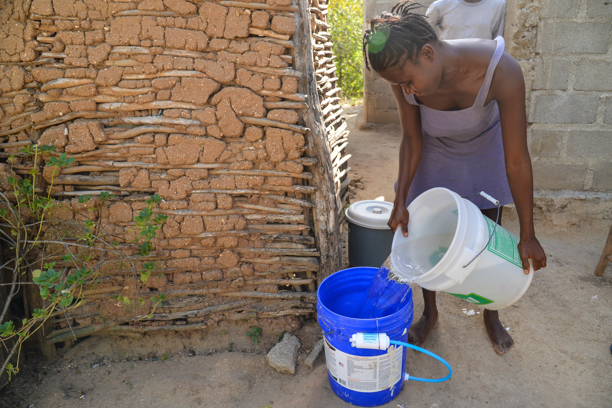 Julianise pouring water from the river into the bucket to be filtered.