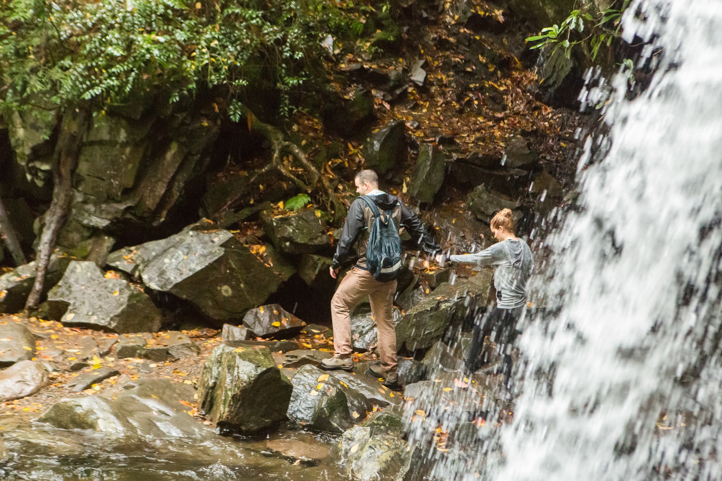 """Josh leads Jaime from behind the waterfall - this is what makes Grotto Falls a """"grotto,"""" as you can walk through a small grotto behind the water."""