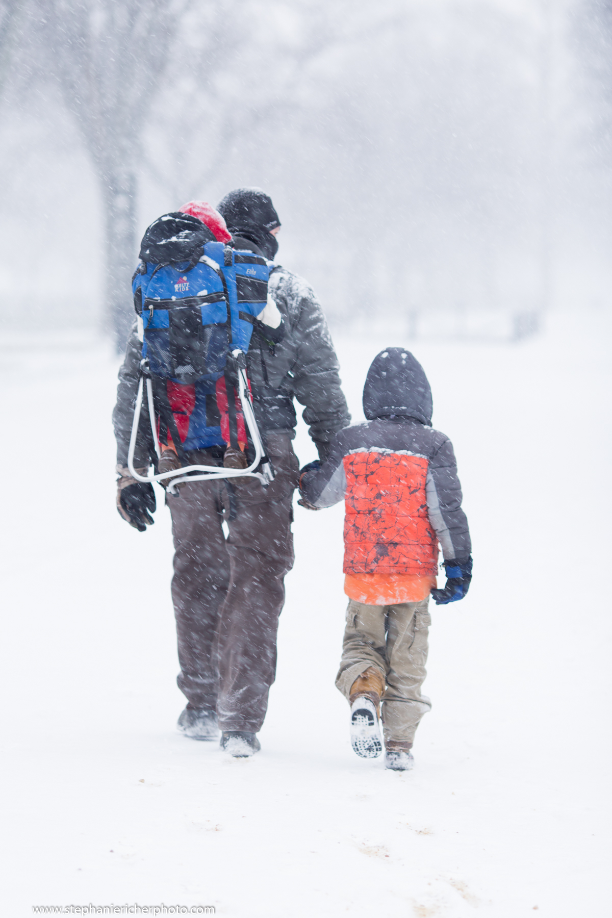 A father and his sons trudge along the National Mall.