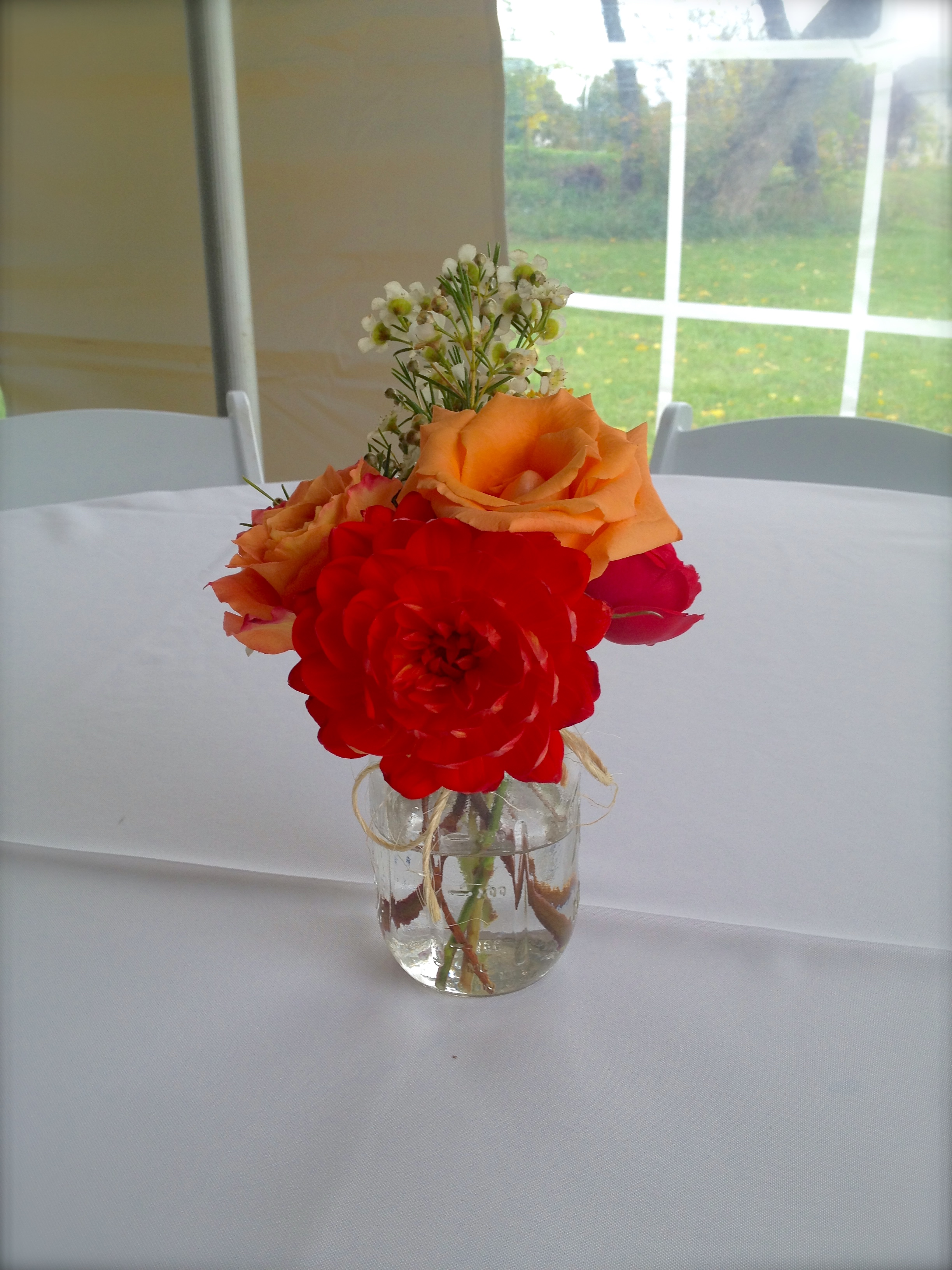 Mason jar centerpiece with garden roses, roses, dahlias and wax flower.