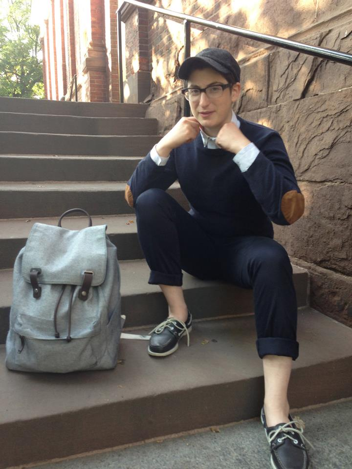 Sonny wearing a wool baseball cap, a checkered Topman button-up, a navy sweater, navy pants, and navy boat shoes. They are sitting on stairs at a brick Harvard building with an Everlane backpack beside them
