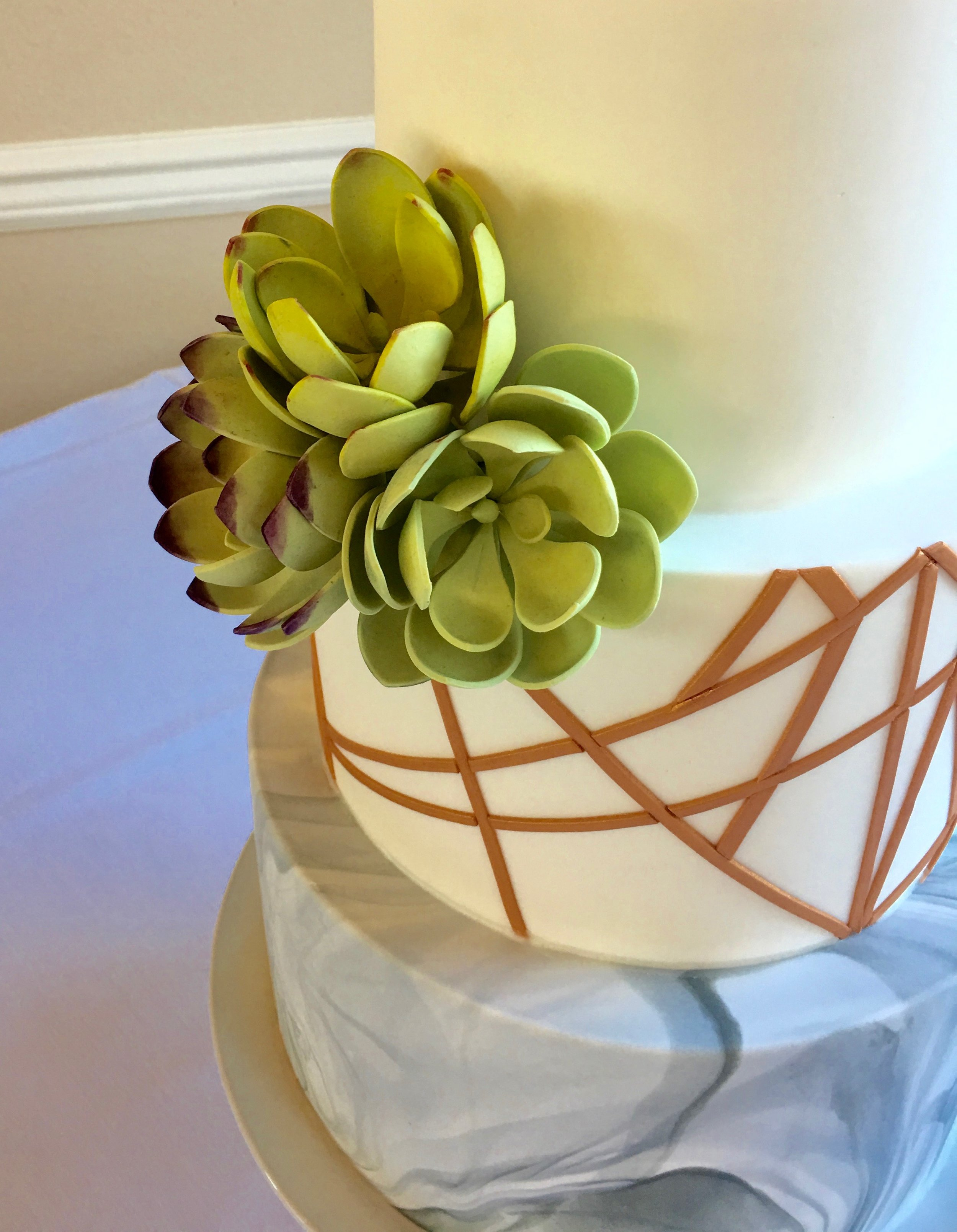 Sugar succulents on rose gold linework cake with marbled base tier. Image copyright Carla Schier.