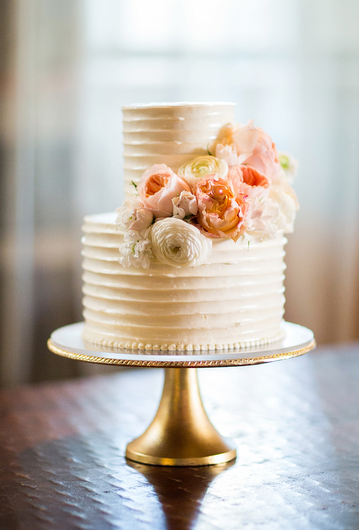 Pleated Buttercream Two-Tiered Cake with Fresh Flowers. Image copyright The Popes Photographers
