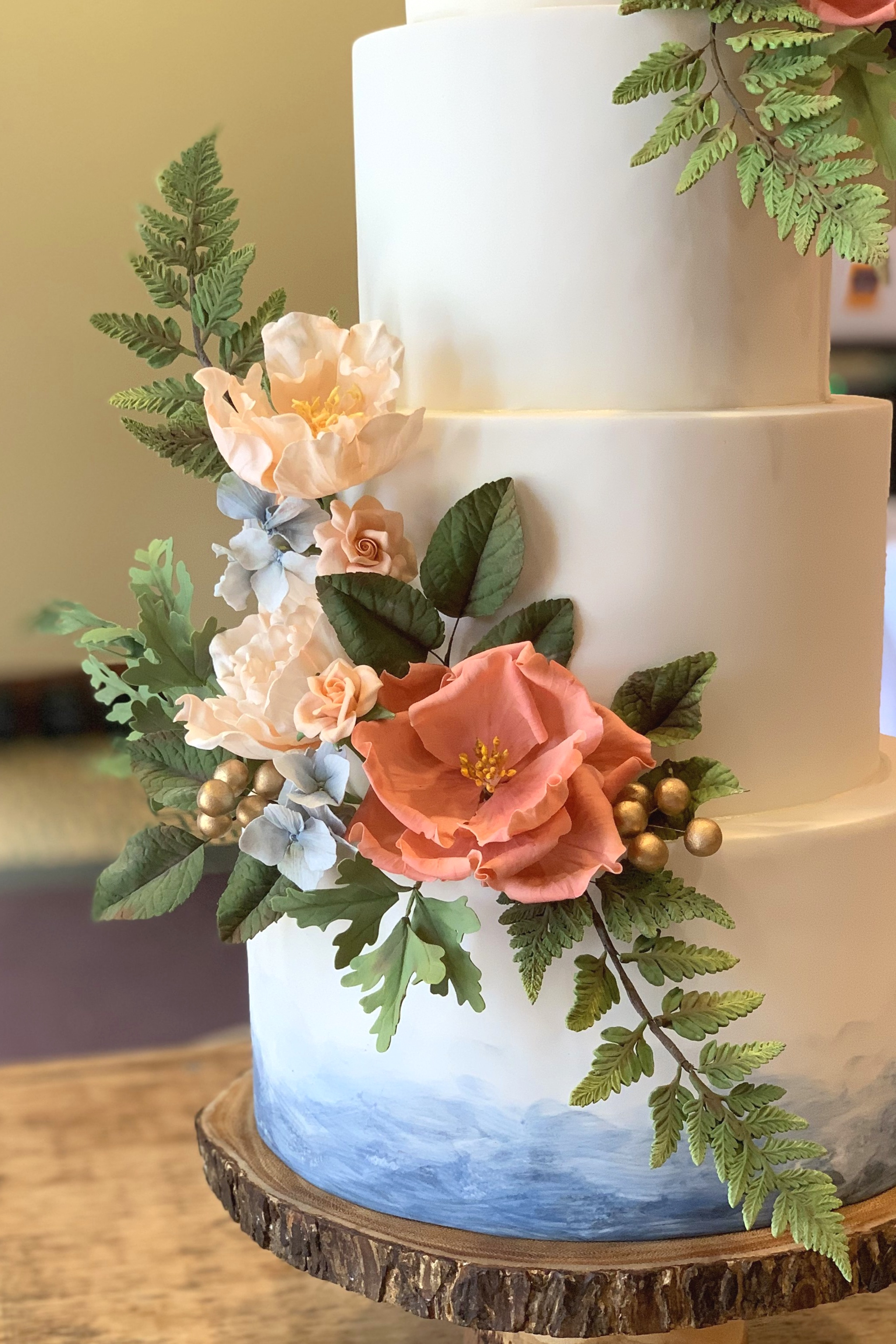 Sugar ferns, climbing roses, roselings, hydrangeas, gold berries, and foliage on a hand painted watercolor cake. Image copyright Carla Schier.