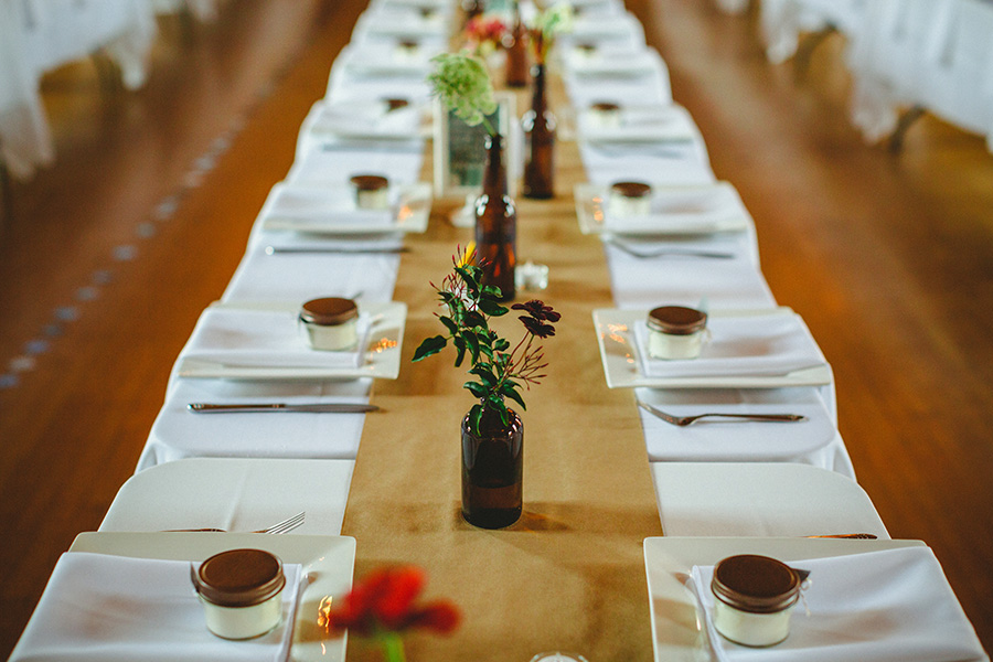 Long farm-style tables draped in white linen with craft paper runners were decorated with various bottles containing flowers, candles, and geometric shapes made of paper for a clean, simple, and unique feel.