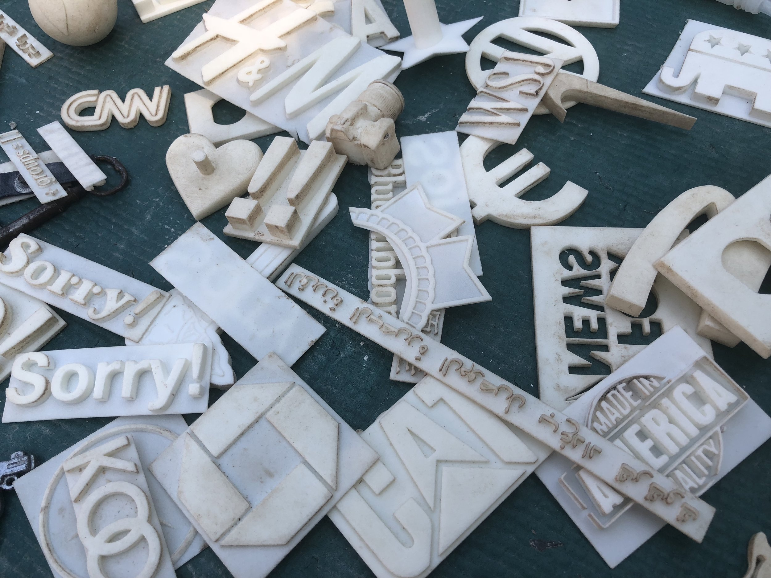 Some  3-d printed logos and other cultural elements laid out in Bob's studio.  Bob creates these works in a 3-d modeling program then prints them on a 3-d printer for imprinting into clay for inclusion in cast wall relief sculptures.