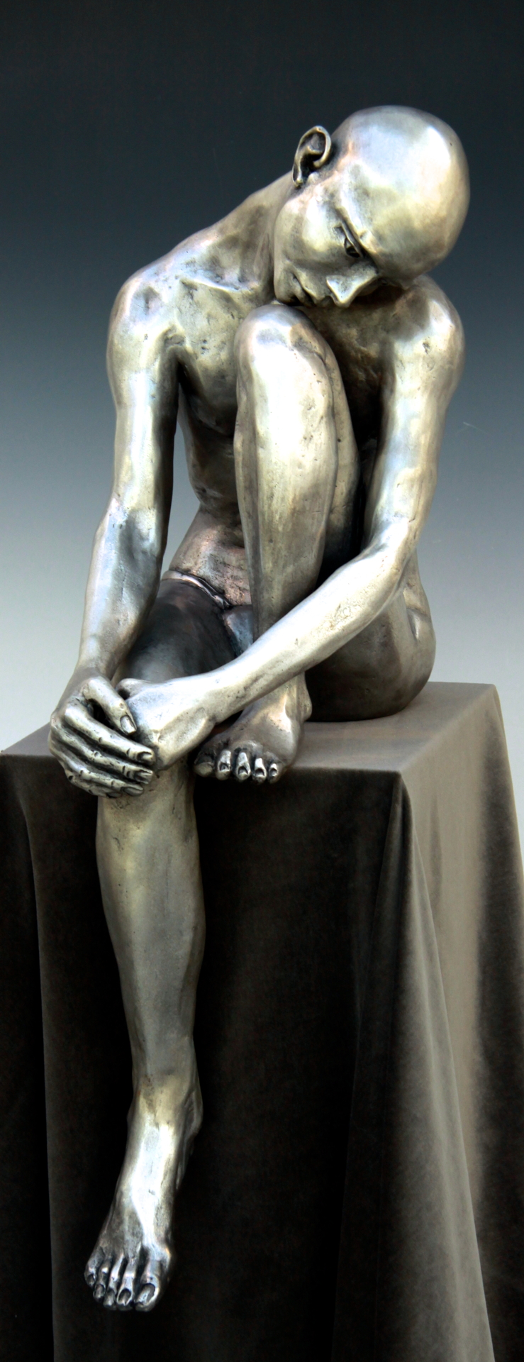 "Seated Man, Head on Knee, bronze edition of 20, silver patina, 26""H x 8""W x 10""D, $6000."