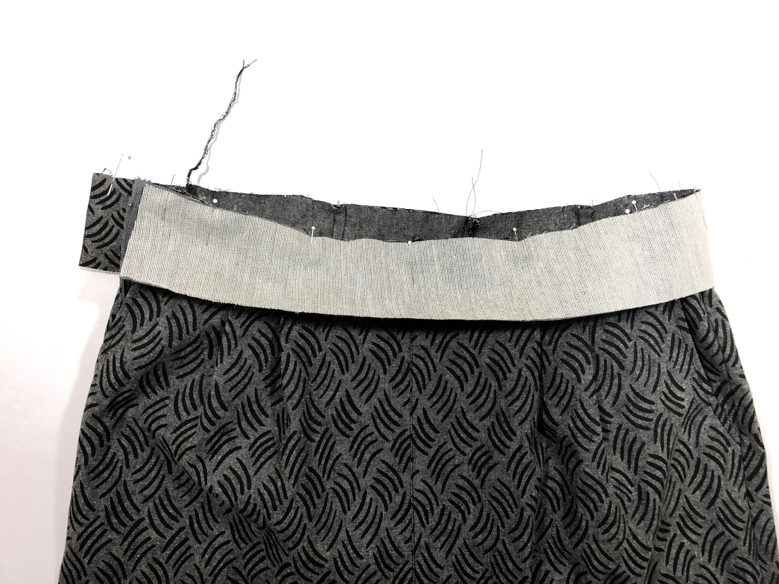 42. With right sides together, pin the interfaced waistband to the top of the pants, matching notches on the waistband to center back seam, center front seam, and side seams on the pants. There should be excess hanging over at the pocket opening.