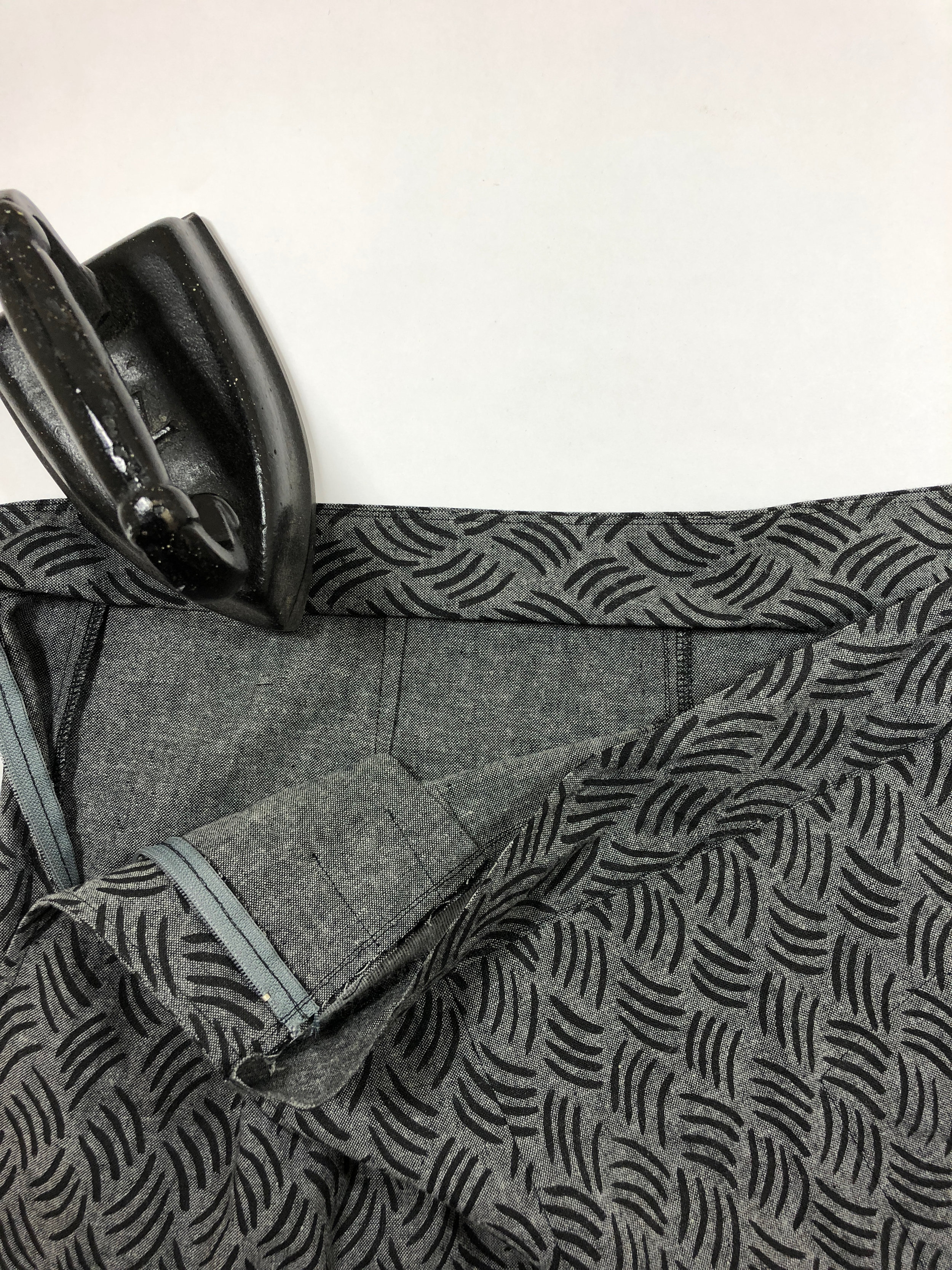 """58. To close up the waistband entirely, fold the remaining seam allowance on the waistband facing up about 3/8"""" to 1/2"""". Just be sure to leave enough hanging past the waistline seam as to catch it with the top stitching from the right side."""