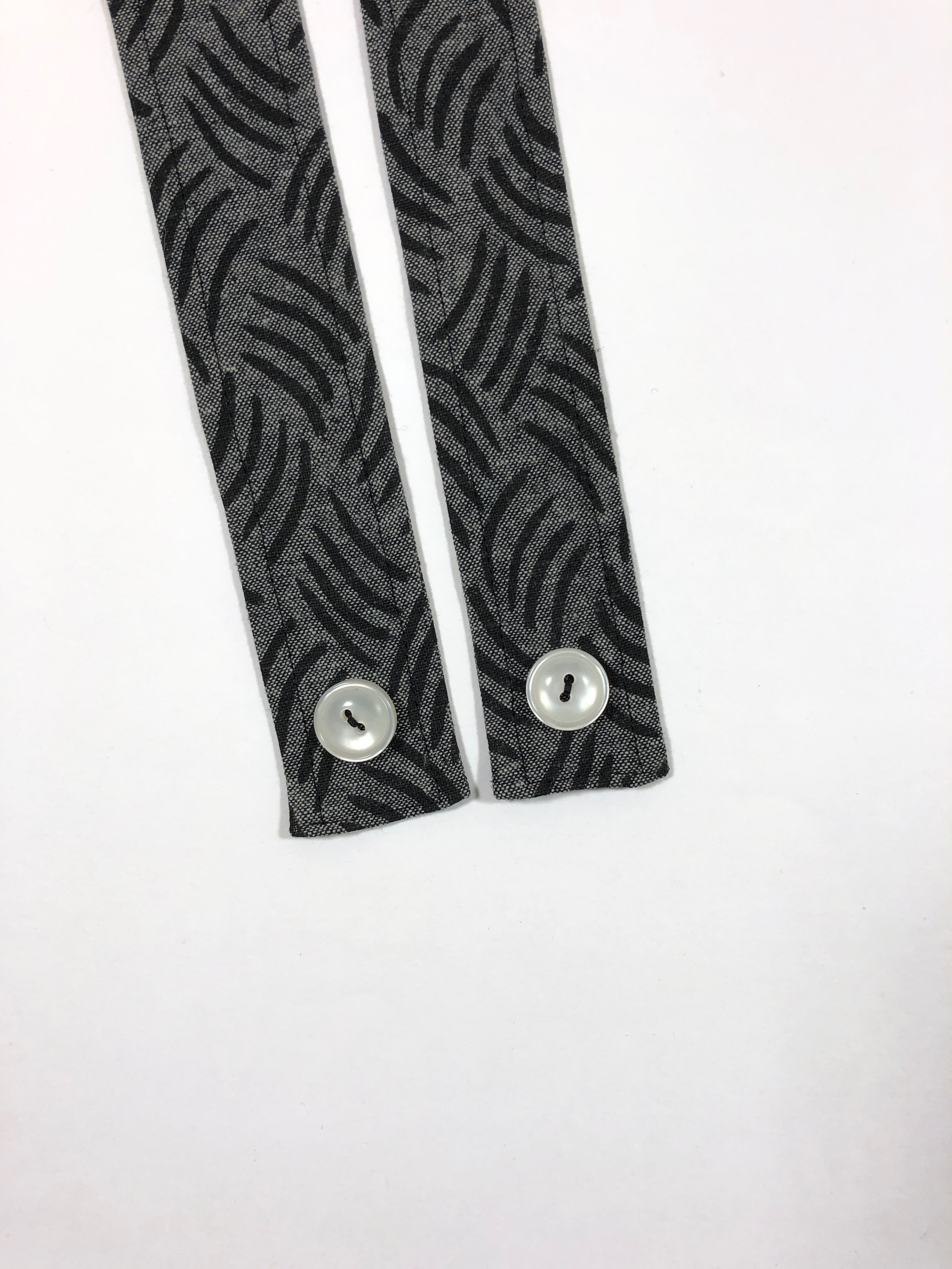 """64. Sew buttons to the straps 1"""" from the bottom edge, and centered."""