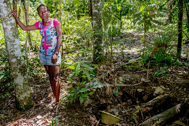 "Martine stands besides her ""toilet"" near her home in Haiti. Martine is a part of the 33% of the world population without access to adequate sanitation. Image: Shiho Fukada,  My Toilet  exhibit"