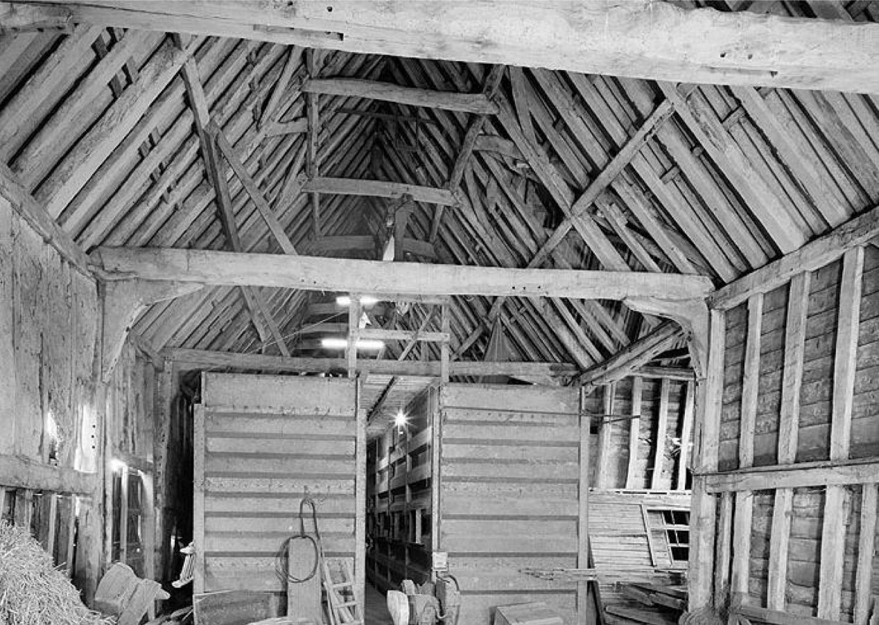 Fig.8 Letheringham Lodge Barn, 1988 (EH Archive, BB92.29105)     4.9 On the 16 March 1966, the Barn at Letheringham Lodge was entered   on the 'Statutory list of buildings of special architectural or historic   inter  est'. The Barn was graded II, and was described in the list entry   (amended 15 August 1988) as follows:     16/3/66. Barn at Letheringham Lodge (formerly listed as barn 170 yards to south-east). GV. II. Barn. Seventeenth century. Timber framed with corrugated iron roof, originally thatched. Eight bays with transepts to one side. South: Brick plinth of Flemish bond. Double doors at right and left, and double loft door to far right. East gable end: Nineteenth century brick outshut to the ground floor with pantile roof. Double door   to the gable above this. North: Lean-to running between the two transepts which are eighteenth century additions with gable ends and double doors. Interior: Close studded walling and arched braces. Tie beams, originally supported on arched braces and now with knee joints. Collars above and wind bracing to the roof. Inserted twentieth century floor at one end.    4.10  As previously stated in the case of the Lodge, for the purposes of establishing the extent of a listed building, the position must be examined as it was at the date of listing of the principal building or, possibly, as it was at 1 January 1969 in relation to buildings listed prior to that date.     4.11  In this instance, the principal building is the Barn at Letheringham Lodge (known today as Long Barn) and it too was added to the statutory list on 16 March 1966. The key dates in this matter are also therefore 16 March 1966 and 1 January 1969.     4.12  The implication of this is that listed building controls today also extend to struct  ures within the curtilage of Long Barn, the 'principal building',   subject again to the provisions of section 1(5) of the 1990 Act and subject again to the structure being ancillary to the principal building at the date of listing, or possibly 1 January 1969 given that the barn was listed prior to this date.    5.0  PHYSICAL LAYOUT, OWNERSHIP AND FUNCTION     5.1  The Lodge together with its former farm buildings and surrounding land, in excess of 250 acres, appears to have remained a single holding in terms of ownership and function throughout the second and third quarter of the twentieth century, and it was only in the 1980s that the farm began to be broken up.     5.2  Prior to the twentieth century, and seemingly apparent throughout both the eighteenth and nineteenth centuries, none of the buildings were historically independent. Similarly, the physical layout of the buildings is one of a group of structures at the heart of a farmstead. Whether accessed from the south or east, the historic layout was one of a farmhouse and associated farm buildings arranged around a   defined area. This area was known as 'Barn Hill' according to   documentary evidence.     5.3  This focal point for the operation of the farmstead was approached, from at least the late nineteen  th century onwards, by way of 'The Drift'   from the south. The seventeenth century residence lies on the north   side of 'Barn Hill', facing south, whilst the principal farm building, the barn, lies on the southern boundary of 'Barn Hill' and faces north   towards the house.     5.4  The timber-framed barn, built about the year 1600, is of eight bays with threshing floors in bays three and six. Evidence in the storey-posts confirms that the barn faced north when first built, and both threshing bays have at a slightly later date been provided with mid-streys on that elevation.     5.5  Farmsteads perform several basic functions. The farmhouse provides shelter for the farmer and his family, and the farm buildings provide for the housing and processing of crops, the storage of vehicles, implements and fodder, and the management and accommodation of livestock. In addition to the house and barn, this typically provides the farmstead with a range of buildings, including stables, cart-sheds, often with granaries above, cow-houses and shelter sheds, as well as enclosed yards for horses and cattle. The relationship between farm- based functions determines how buildings are arranged around the farmstead, and how they relate to the house.    5.6  The farm buildings immediately to the west of the Lodge, which similarly   relate to 'Barn Hill' and are accessed by 'The Drift', are largely of mid  - nineteenth century construction. They include cart-sheds, granary, cow-house, stables, and shelter sheds.     5.7  The early eighteenth century survey plan indicates the prior existence of structures in this location, none of which survive today. These lost   structures are depicted on Kirby's 1732 plan in such a manner as to   suggest that there existed a small group of domestic buildings in the location of the nineteenth century farm buildings. The buildings drawn appear to represent the existence in 1732 of a dwelling of seventeenth century date situated immediately to the west of the moat, together with a contemporary, detached stable range further to the west.     5.8  Early nineteenth century plans show the existence of other lost structures, most probably agricultural in terms of function, which were located in the south-  west corner of 'Barn Hill'  . These structures lay between the domestic group and the barn, but were again sited around the periphery   of 'Barn Hill', adjacent to the field known as 'cartlodge field' or 'cartlodge piece'.     5.9  The existing farm buildings in the north-  west corner of 'Barn Hill',   situated in close physical proximity to and forming a group with the Lodge, are either of timber-frame construction of a style typical of the nineteenth century, or are of brick construction of a uniform type and bond which is repeated on the range also erected in the mid- nineteenth century next to the barn.     5.10  Buildings 3 and 4 on a plan dated May 1999 are today used as annexe   accommodation with the Lodge and are known as 'Chestnut Cottage'. This is a building of mid  -nineteenth century date which in 1919 was being used in a manner ancillary to the use of the Lodge as a dwelling. At some point after that date, and in the early twentieth century, it was converted to a separate residence, being known as   'Lodge Farm Cottage' in the 1960s and early 1970s.     5.11  A nineteenth century wall physically separates the garden of the Lodge from the meadow   known as 'Barn Hill'   to the south, although the bounds of this meadow, within which all the farm buildings are arranged, does provide a physical limit so as not to extend to include the whole of the holding. An orchard is situated to the north of the   Lodge and additional garden to the east, both of which are clearly defined in their extent.    5.12  To the west, and adjacent to the mid-nineteenth century range of former piggeries and outhouses, is located a building that was described in the 1919 sale particulars (SROI, f SC142/1) as a   'brick and tiled hackney stable, with two stalls and loose box'  . This building was   listed on the sales particulars as being with the 'residence', and whilst   being ancillary to the Lodge prior to its conversion to a holiday cottage in 1989/90 (C/9605, approved 1 February 1989), it is now part of Lodge Farm.     5.13  This north facing structure, shown as building 5 on the May 1999 plan, had an access way between it and the former piggeries and outhouses. This is evident on the 1884, 1904 and 1975 OS maps, as well as the 1945 aerial photograph. This track, which also provided access from the farm yards to the fields to the north, no longer survives following the introduction of a separate residential use into building 5 and the subsequent erection of a boundary fence.     5.14  The facts of the matter in relation to the Barn are largely as that for the Lodge, that is,   the common access by way of 'The Drift', the physical   layout of the farm buildings aro  und 'Barn Hill', the single holding in   terms of ownership and function throughout the second and third quarter of the twentieth century, including both 1966 and 1969, and none of the buildings being historically independent.     5.15  The physical layout of the barn and the mid-nineteenth century buildings is one of a group of structures at the heart of a farmstead. Whether accessed from the south or east, the historic layout was one of a barn and associated farm buildings arranged around a defined area. This   area was known as 'Barn Hill' according to documentary   evidence.     5.16  This focal point for the operation of the farmstead was approached,   from at least the late nineteenth century onwards, by way of 'The Drift'   from the south. The barn lies on the southe  rn boundary of 'Barn Hill',   and the mid-nineteenth century buildings lie to the north-west corner of   'Barn Hill'.    5.17    The barn, built about the year 1600, faced into the area known as 'Barn Hill'. Barns, as in this instance, are normally the oldest and m  ost impressive farm building on the holding. They provided for the processing and storage of crops and were regarded as status symbols, with the size of the barn reflecting the size of holding and the wealth of its owner.     5.18  The other buildings of the farmstead, including stables, cart-sheds, often with granaries above, cow-houses and shelter sheds, typically provide functions that are ancillary and subordinate to that of the barn. The age and construction of the farm buildings immediately to the west of the Lodge have been described earlier.     5.19  They represent a nineteenth century phase of redevelopment of the minor buildings on the farm whilst the main building, the barn, was retained. The association between the farm buildings is also demonstrated by the contemporary alterations and additions to the barn, as well as the construction of a new detached range.    5.20 Letheringham Lodge and the size of holding.         Year,   Year,   Acreage,   Occupier,   Reference     1732,   389 (approx.),   Surveyed by J. Kirby    1790s,   SROI, HD11.475/103    Early C19,   William Cooper,   SROI, HD11.475/563    1830s,   389 (approx.),   SROI, HD11.475/596    1837,   388 (approx.),   William Toller    1842/3,   William Toller,   SROI, FDA165/A1/1a+b   362 (approx.),   Mr Toller,   SROI, HD11.475/562    1919,   330 (approx.),   Mr Capon,   SROI, f SC142/1    1987,   242 (approx.),   Mr M.R. Clough,   C/9605    1991,   Mr M.R. Clough,   C/91/0962    Fig.9 The size of holding at Letheringham Lodge, 1732-1991