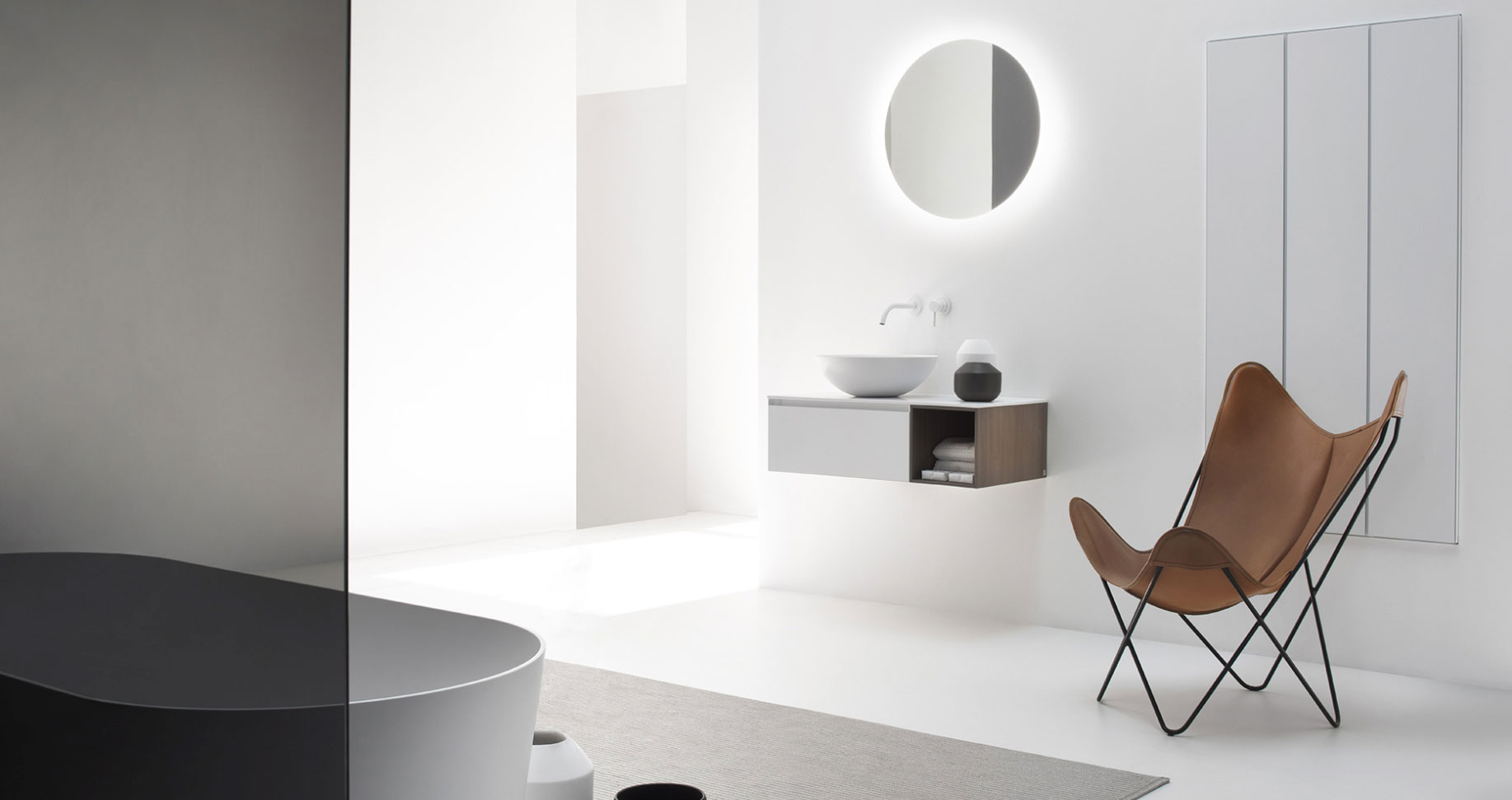 small floating bathroom vanity with circular sink and circular backlit mirror
