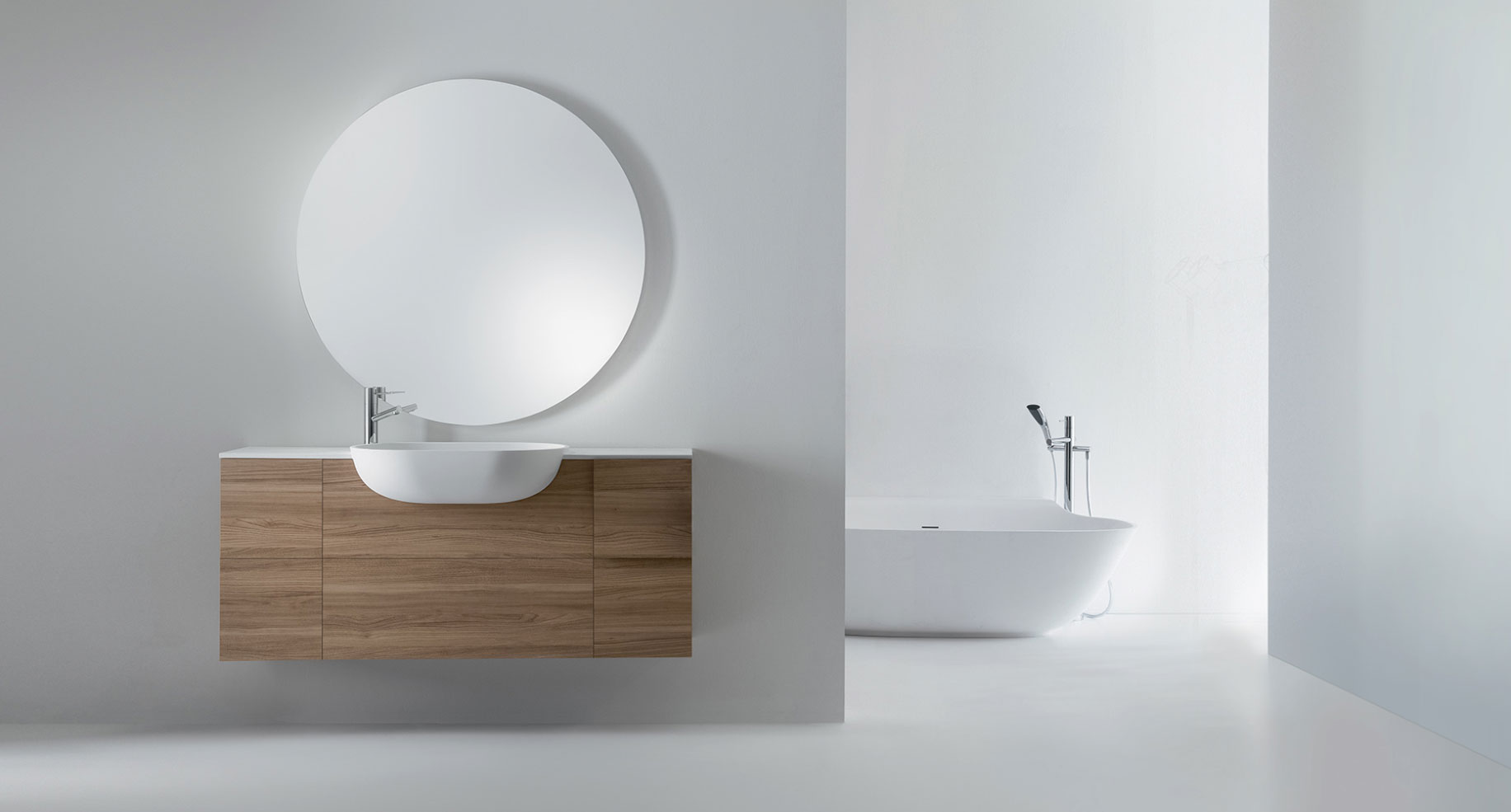 Floating wooden bathroom vanity with circular mirror and modern tub design