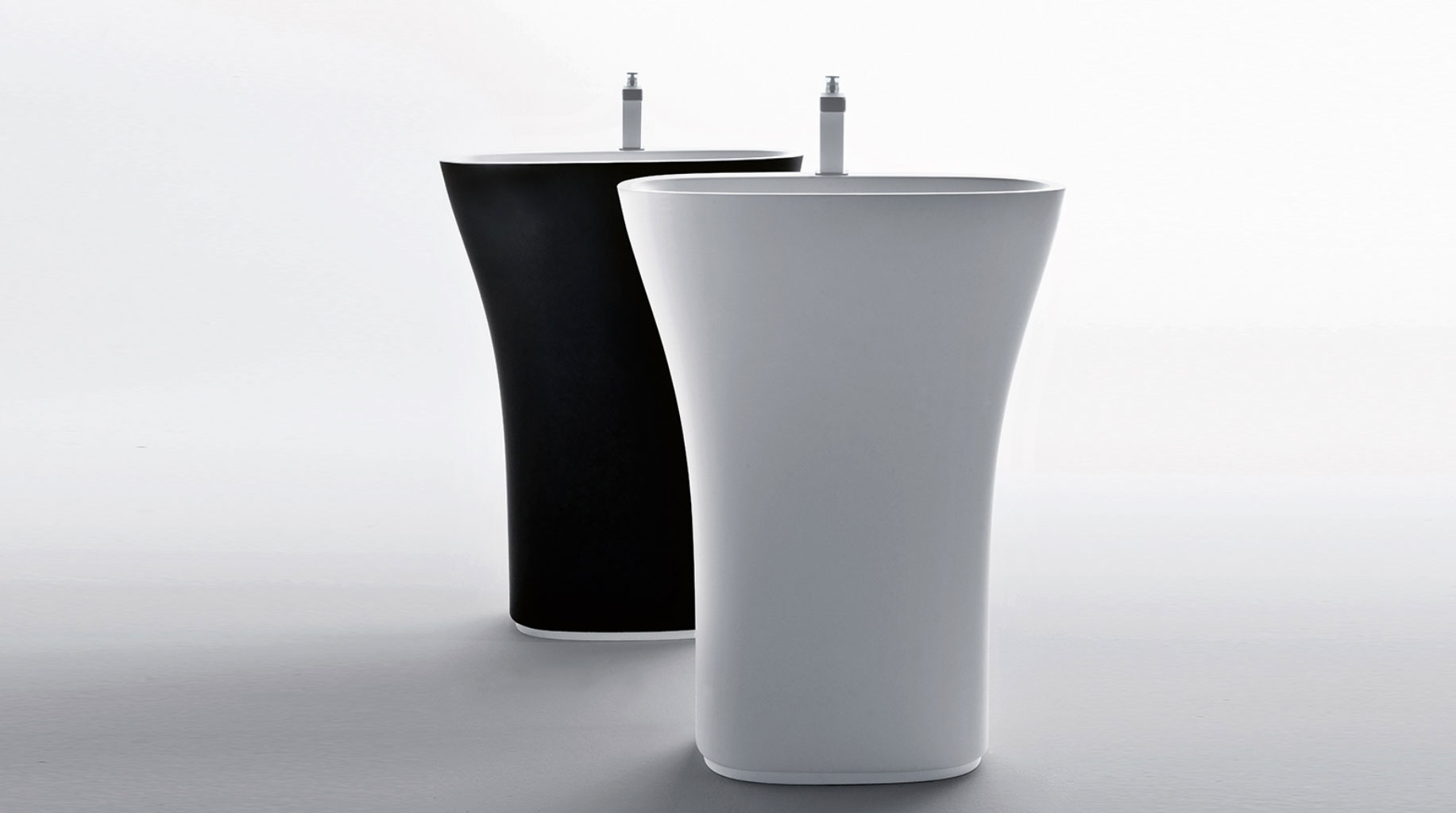 two curved standing wash basins in black and white
