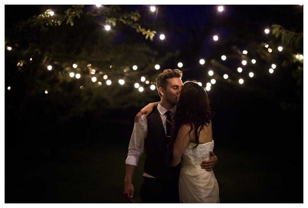 24-DanijelaWeddings-KurtzOrchards-Niagaraonthelake-wedding-couple-rain-kiss-twinklelights.JPG