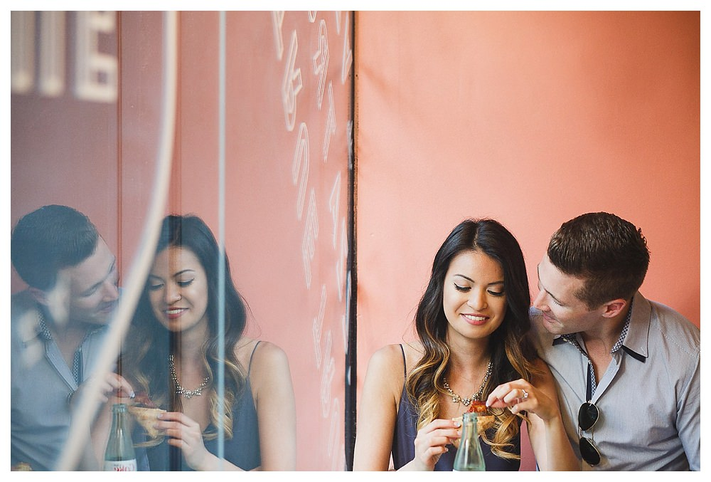 In the window of the pizza store, the groom caught his bride's reflection.