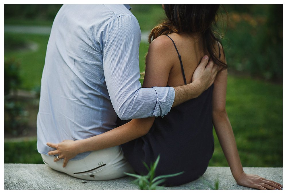 The gentle hold of his hand on her back speaks of love at their engagement photo shoot.