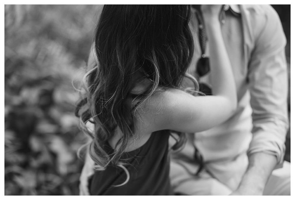 The bride's beautiful hair embraces her shoulders while she embraces her groom for their engagement photos.
