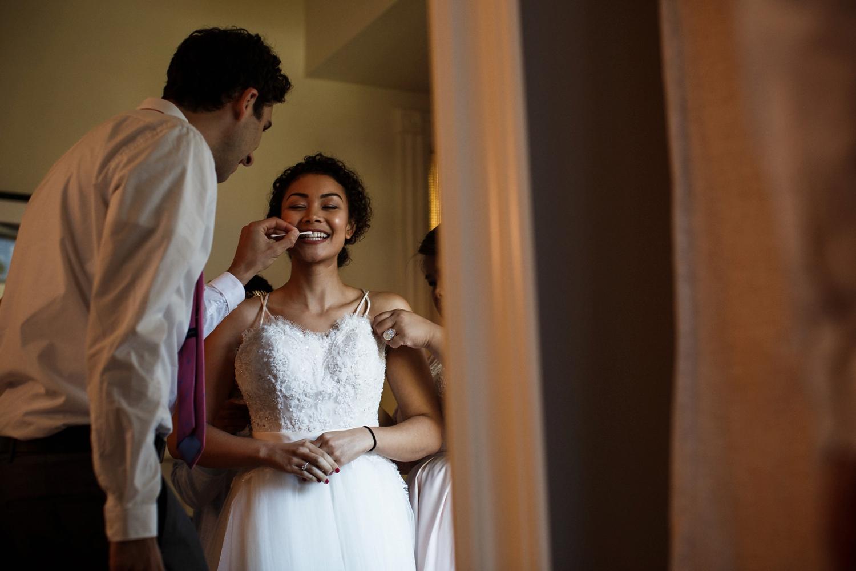 Bride getting dressed at Gladstone Hotel for wedding.