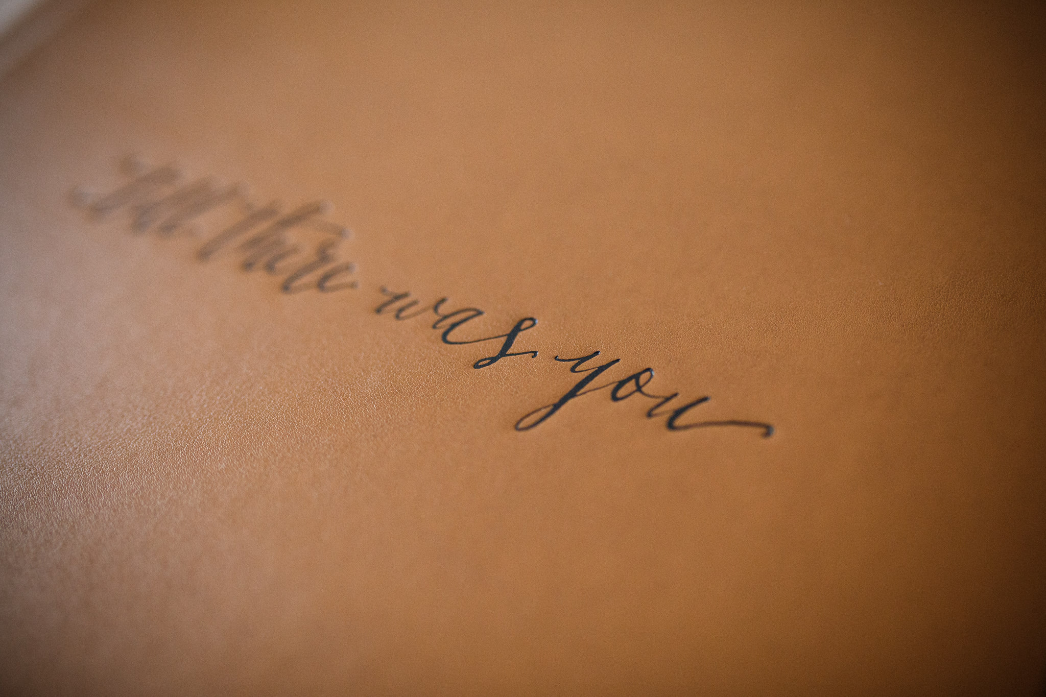 Name embossing on photo album cover in leather.