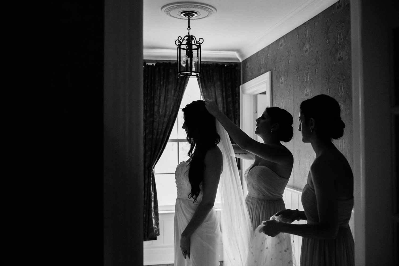 Bridesmaids putting veil on bride for Kurtz Orchards wedding.