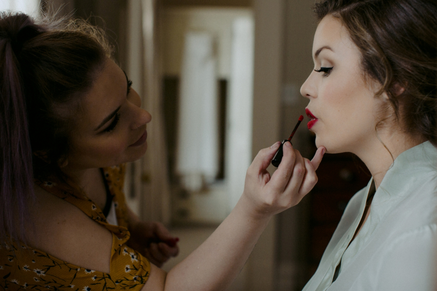 Bride putting on red lipstick at Langdon Hall wedding.
