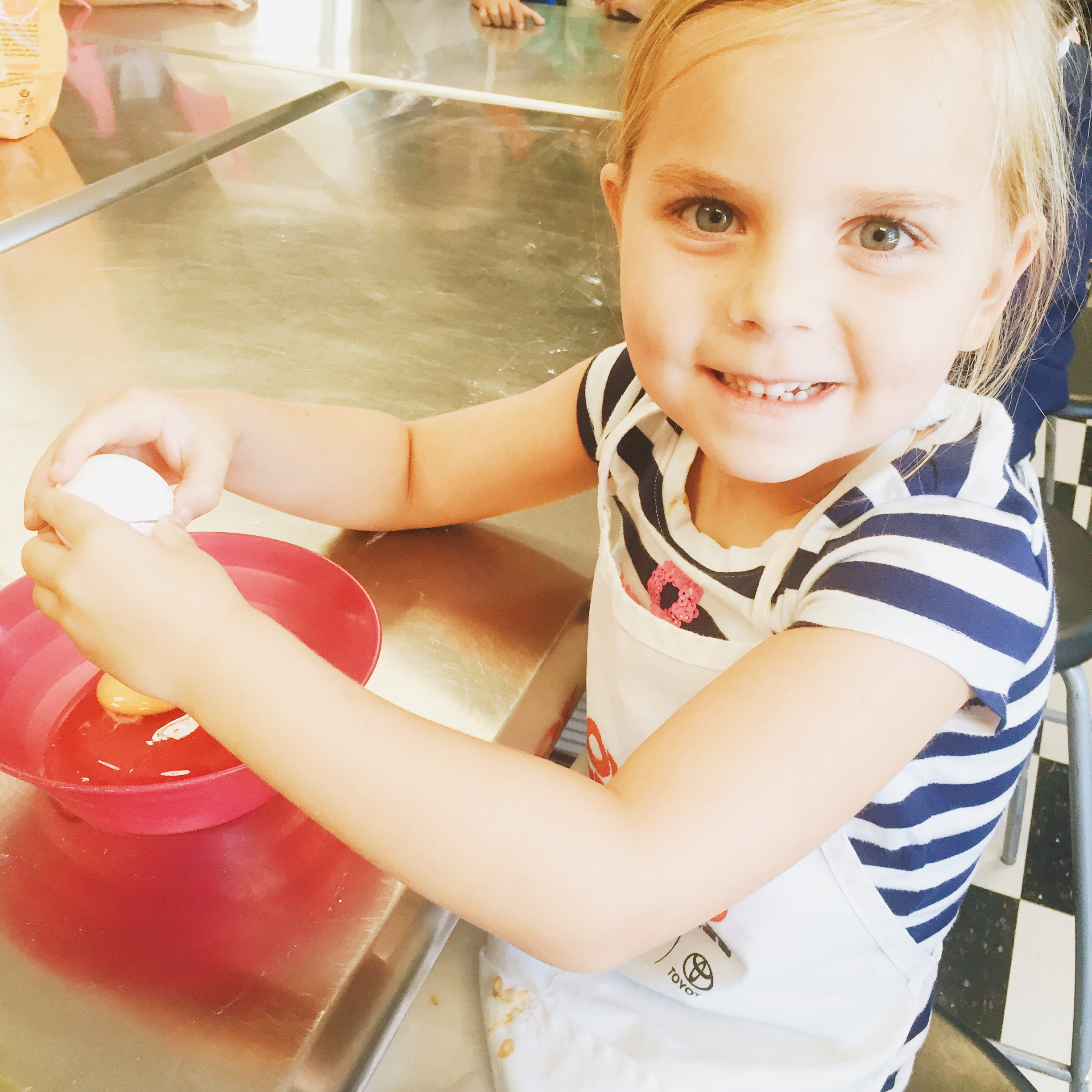 Young Chefs Academy Camper, Halle, cracking an egg in the kitchen