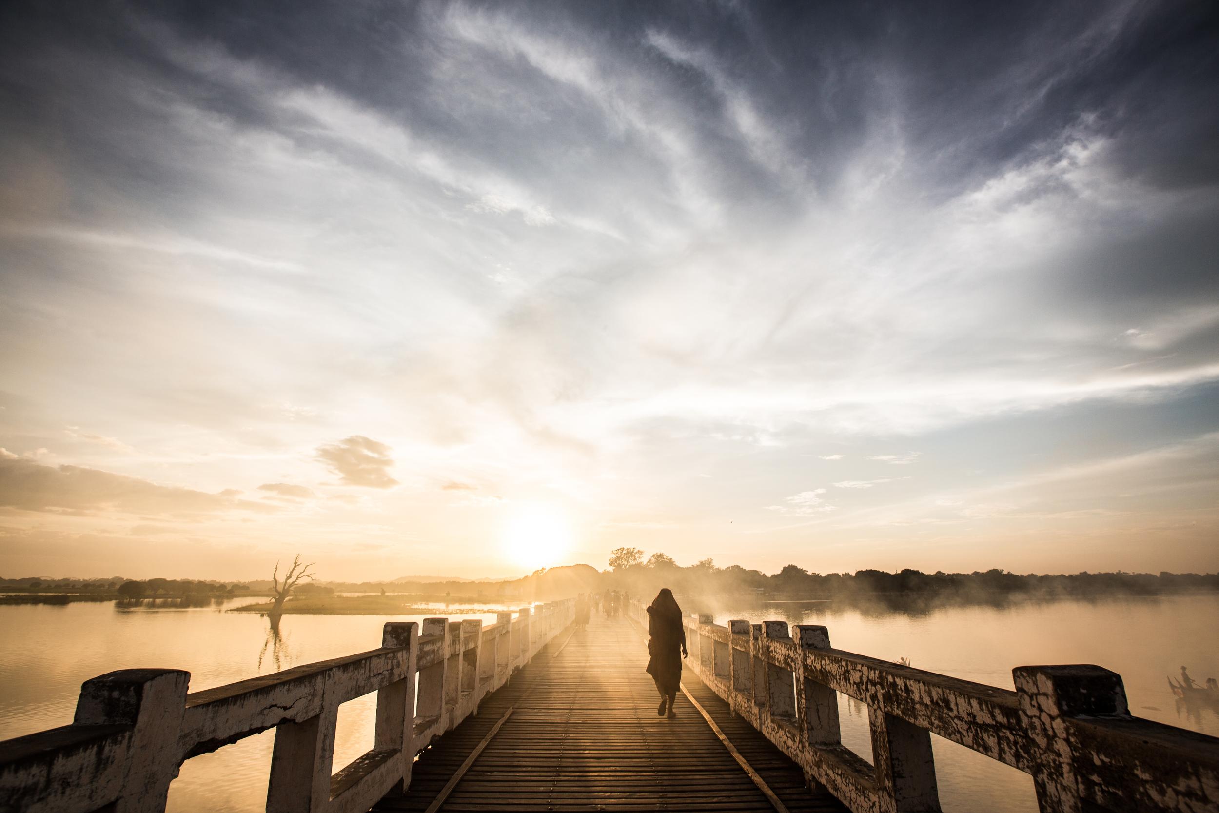 A monk crossing a teak bridge in Amarapura, Myanmar (Burma).