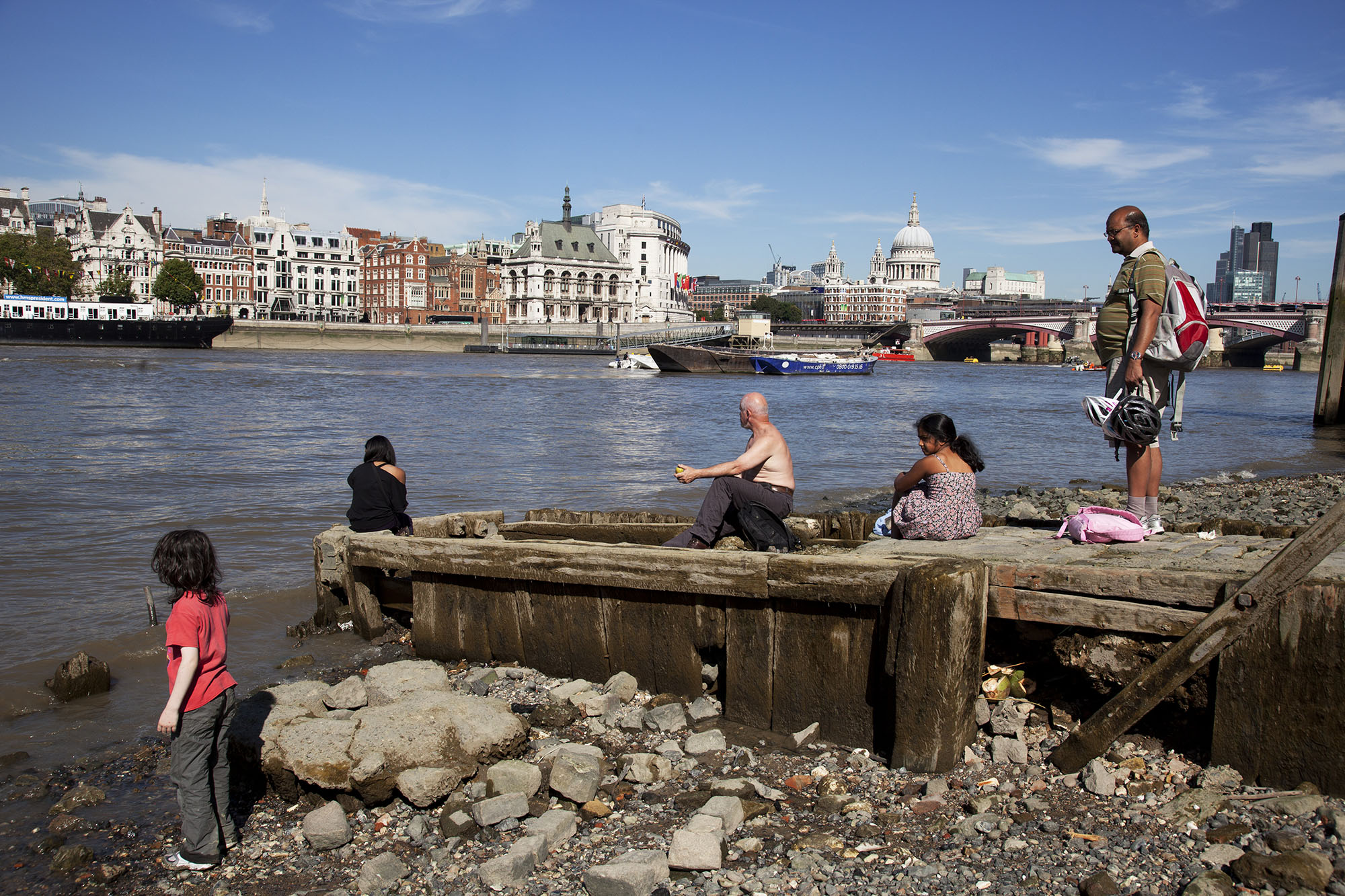At low tide on the South Bank riverfront, people gather to sit on an old jetty