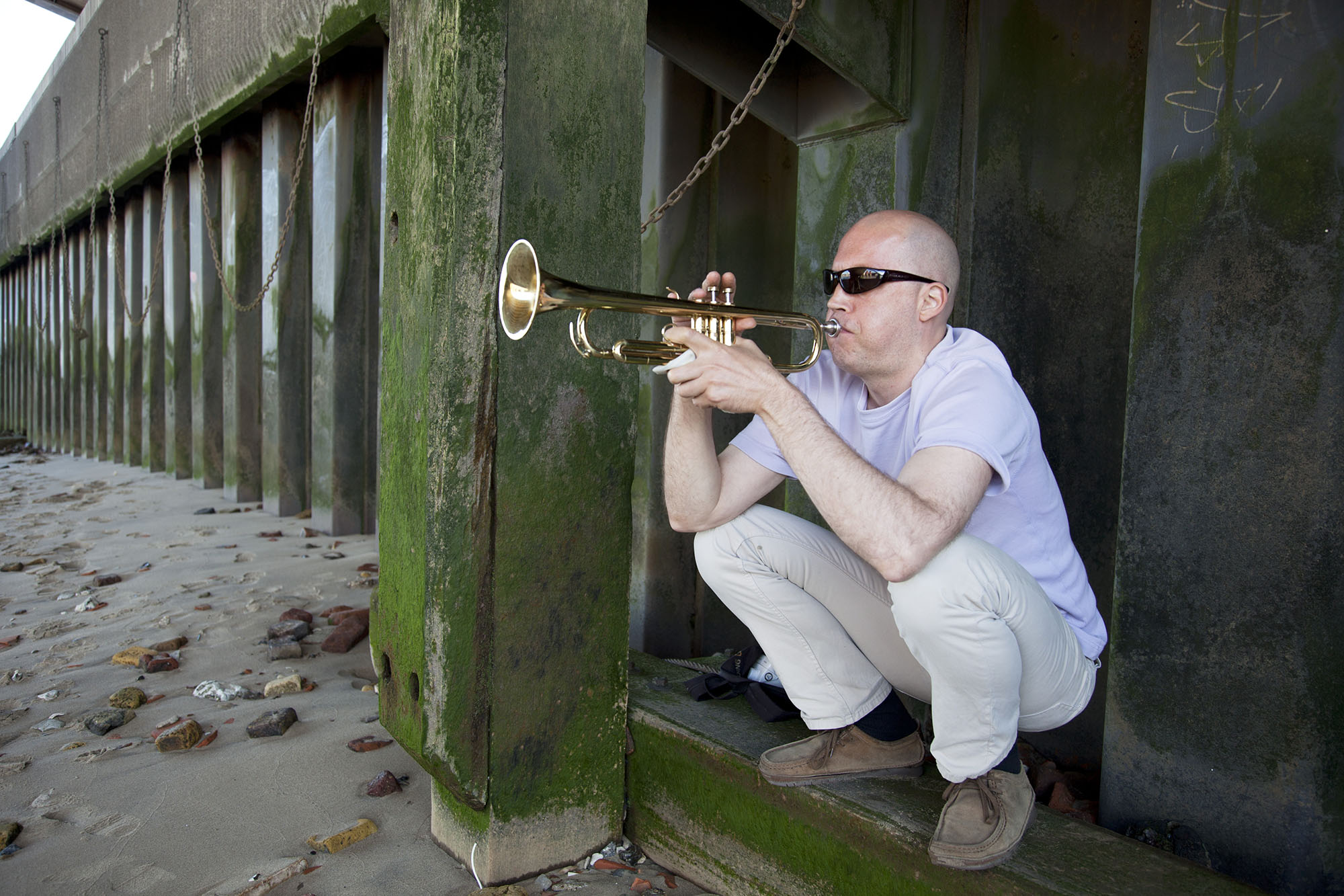 Man plays a trumpet underneath Blackfriars Bridge on the shore of the River Thames.