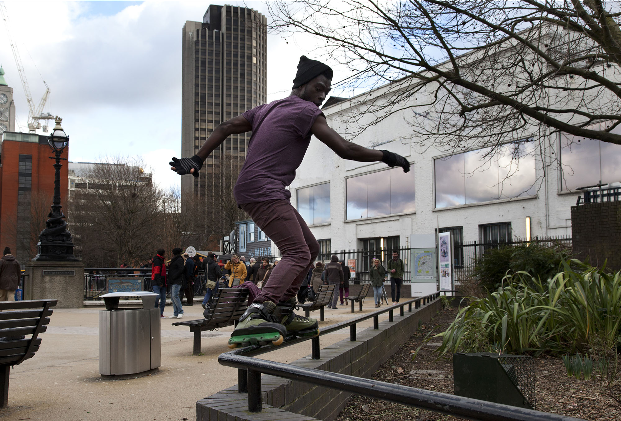 'Aggressive' inline skater performs a glide trick along a rail on the South Bank walkway.