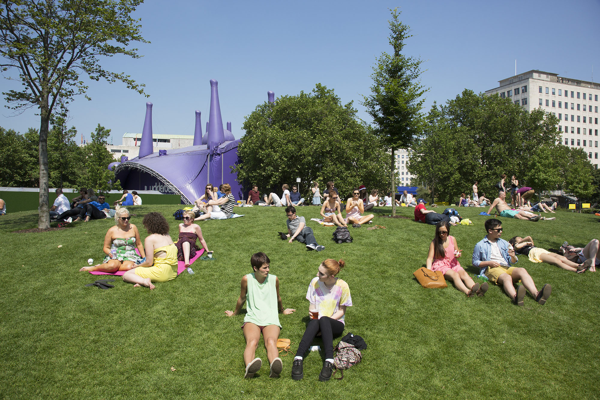People gather on the grass in the sunshine at Jubillee Gardens on the South Bank.