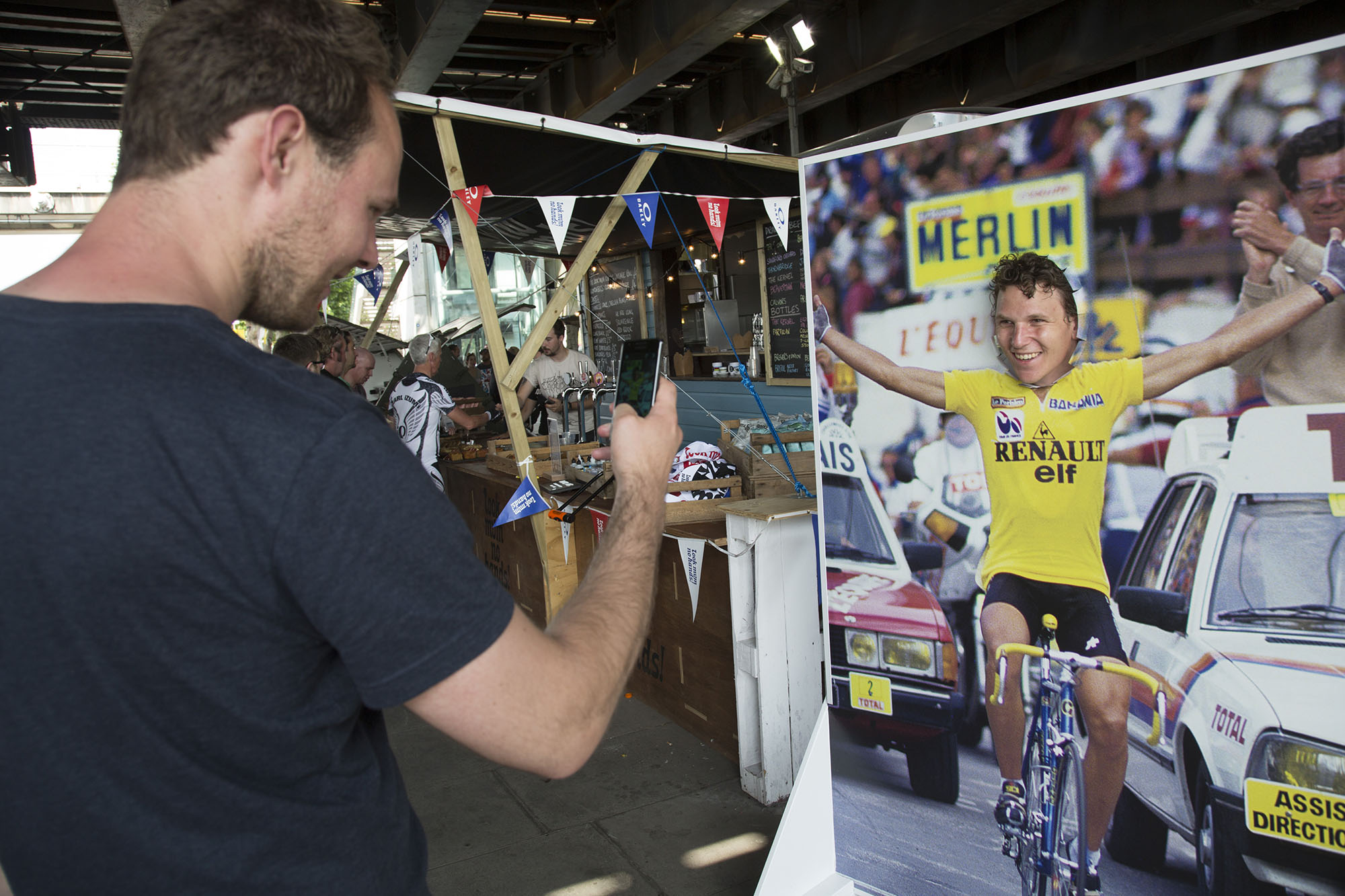 Man has his Tour de France yellow jersey photo taken at the 'Look Mum No Hands' cycling cafe under Hungerford Bridge.