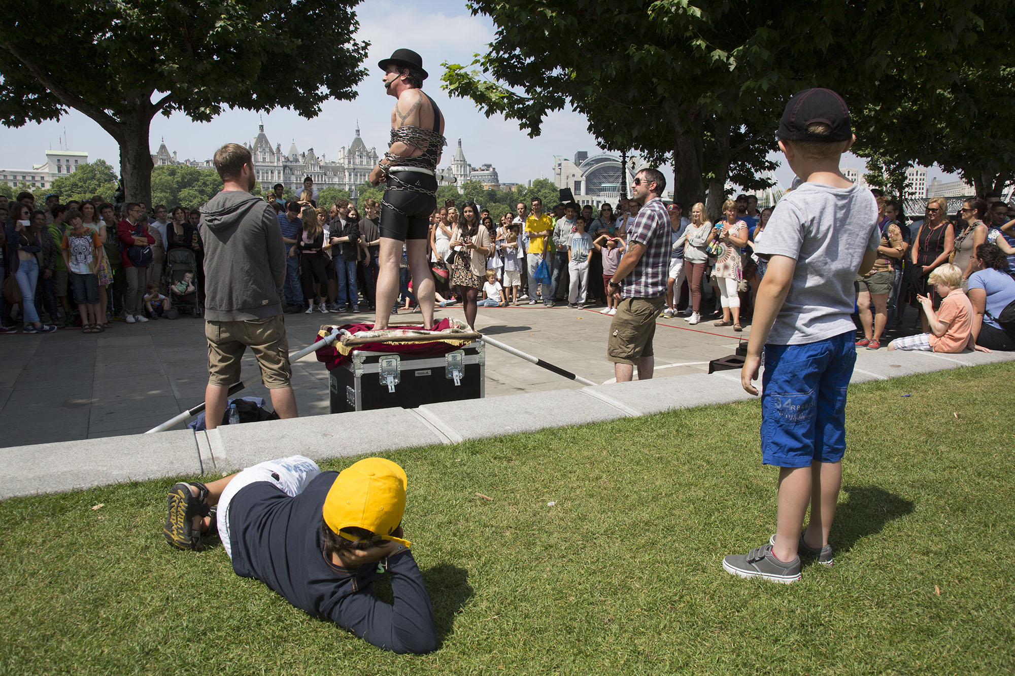 Street performing escapologist Tony Roberts delights crowds with his show on the South Bank walkway.