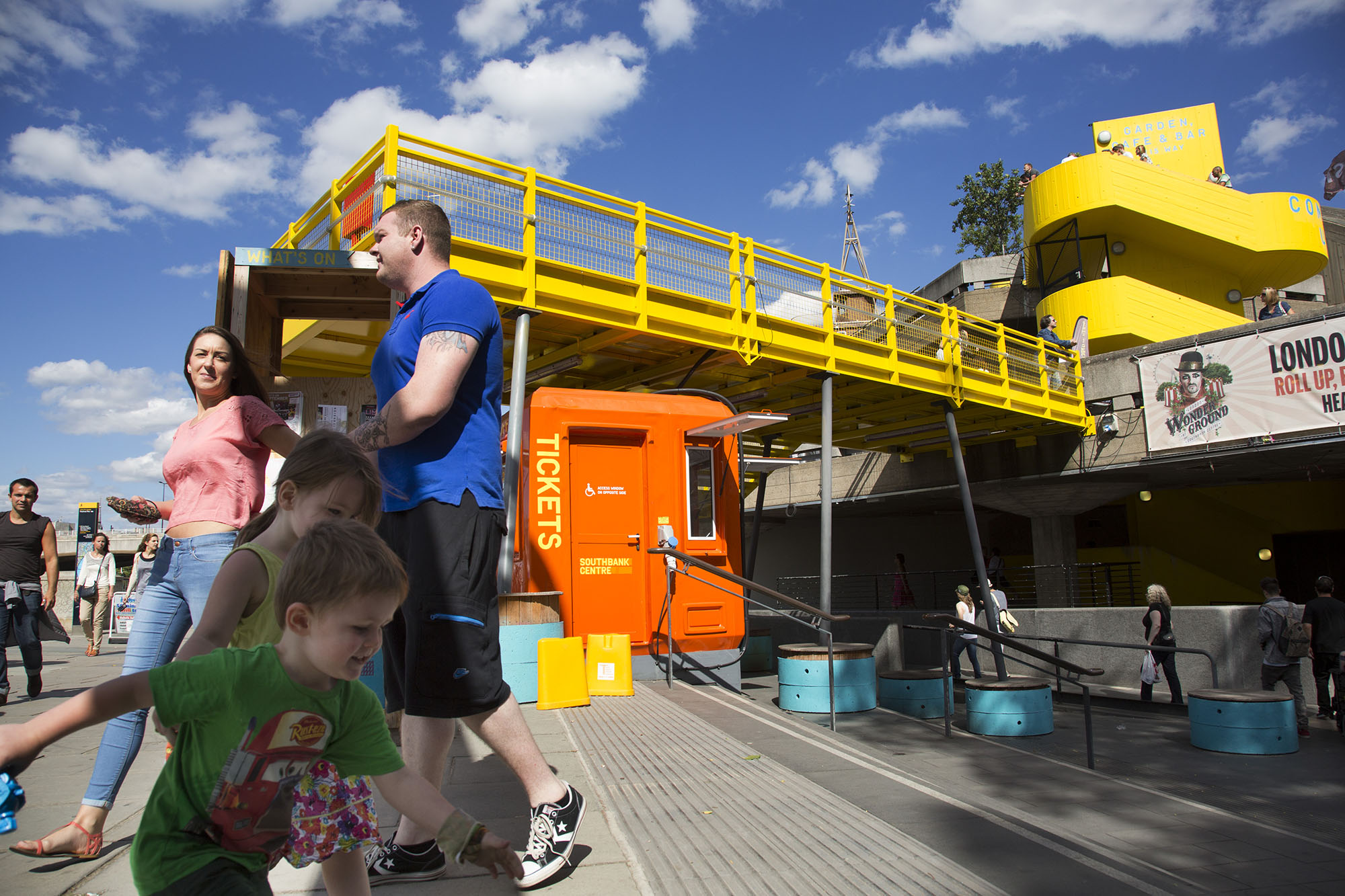 Kids playing near the yellow gantry walkway which joins a terrace to the main walkway on the South Bank.