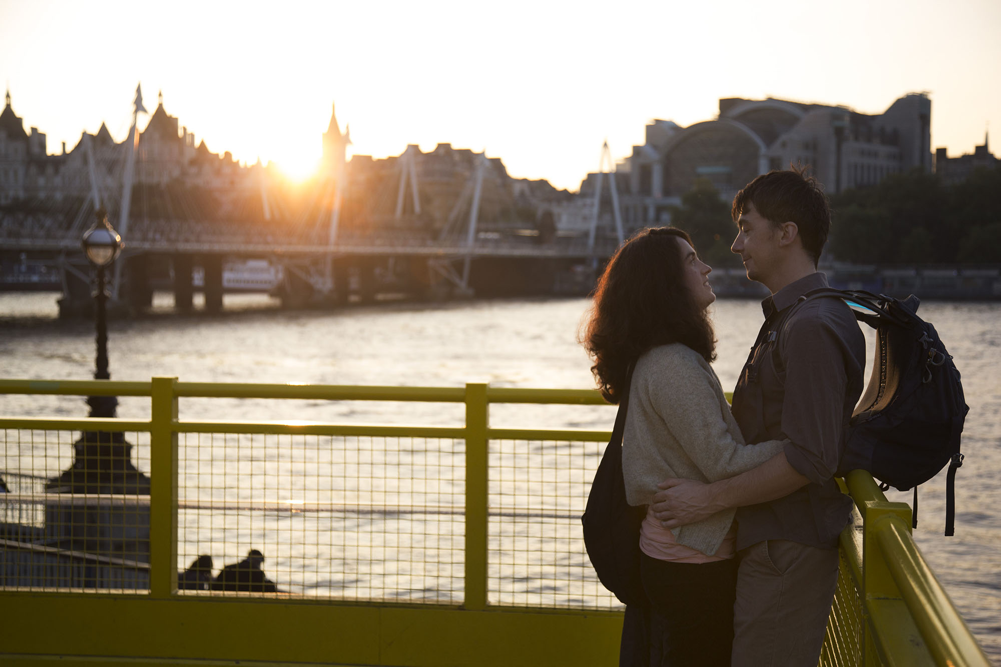 Lovers embrace at sunset on the yellow gantry beside the Royal Festival Hall terrace.
