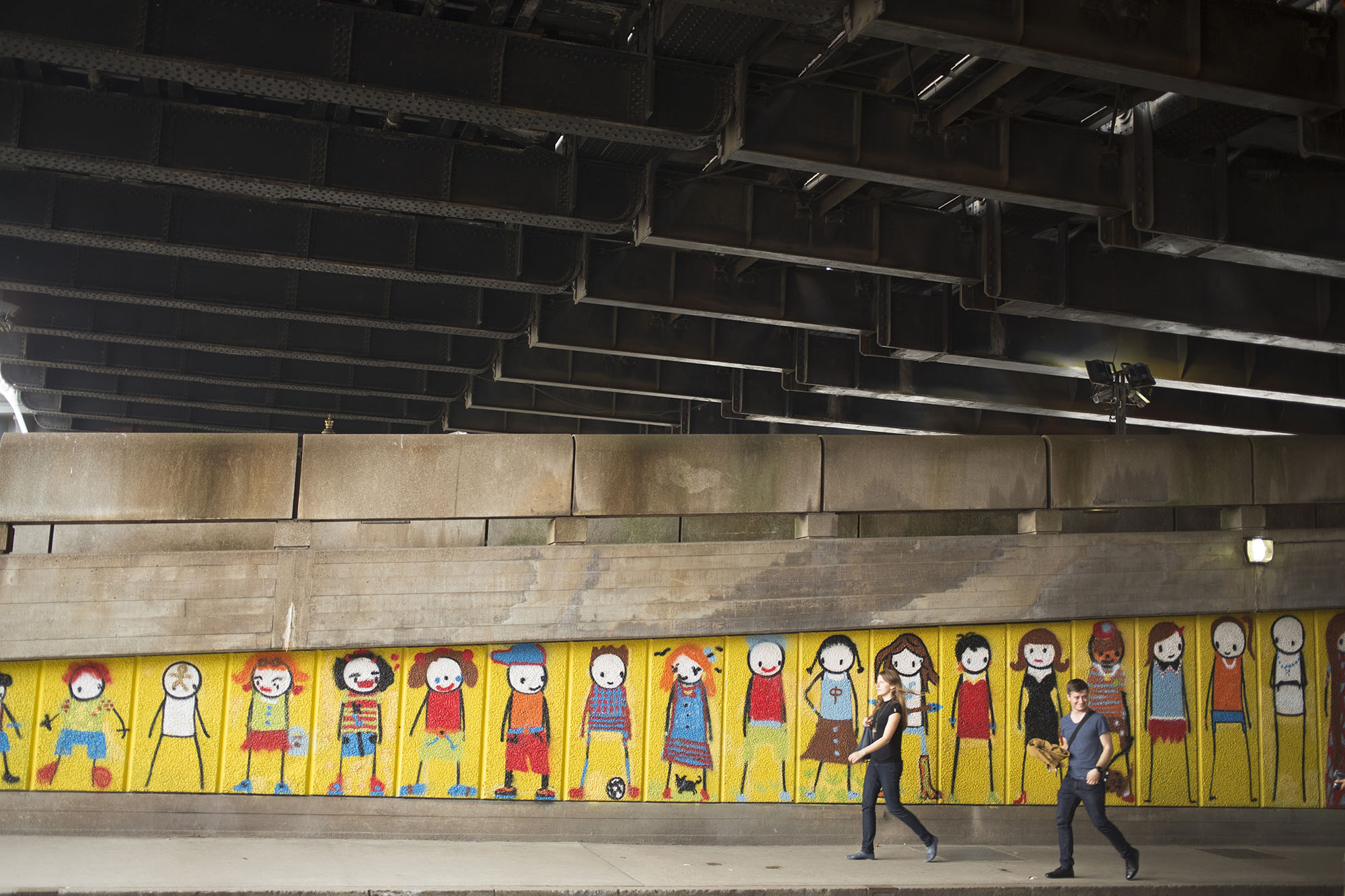 Street art graffiti under Hungerford Bridge showing characters growing up by artist Stik.