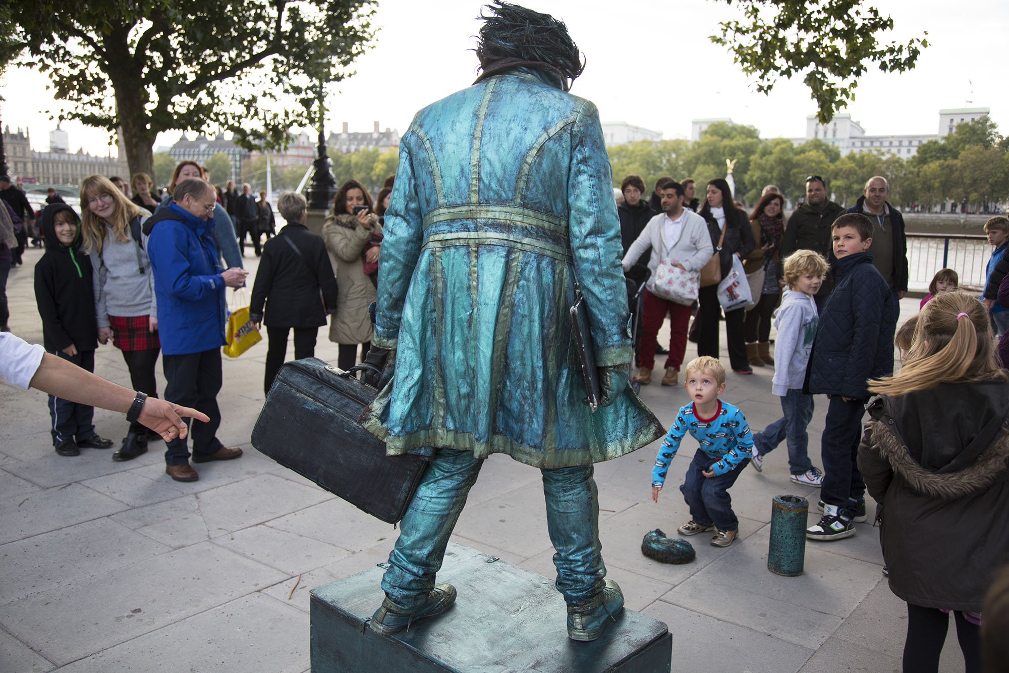 Children interact with a living statue artist who does not blink for hours at a time.