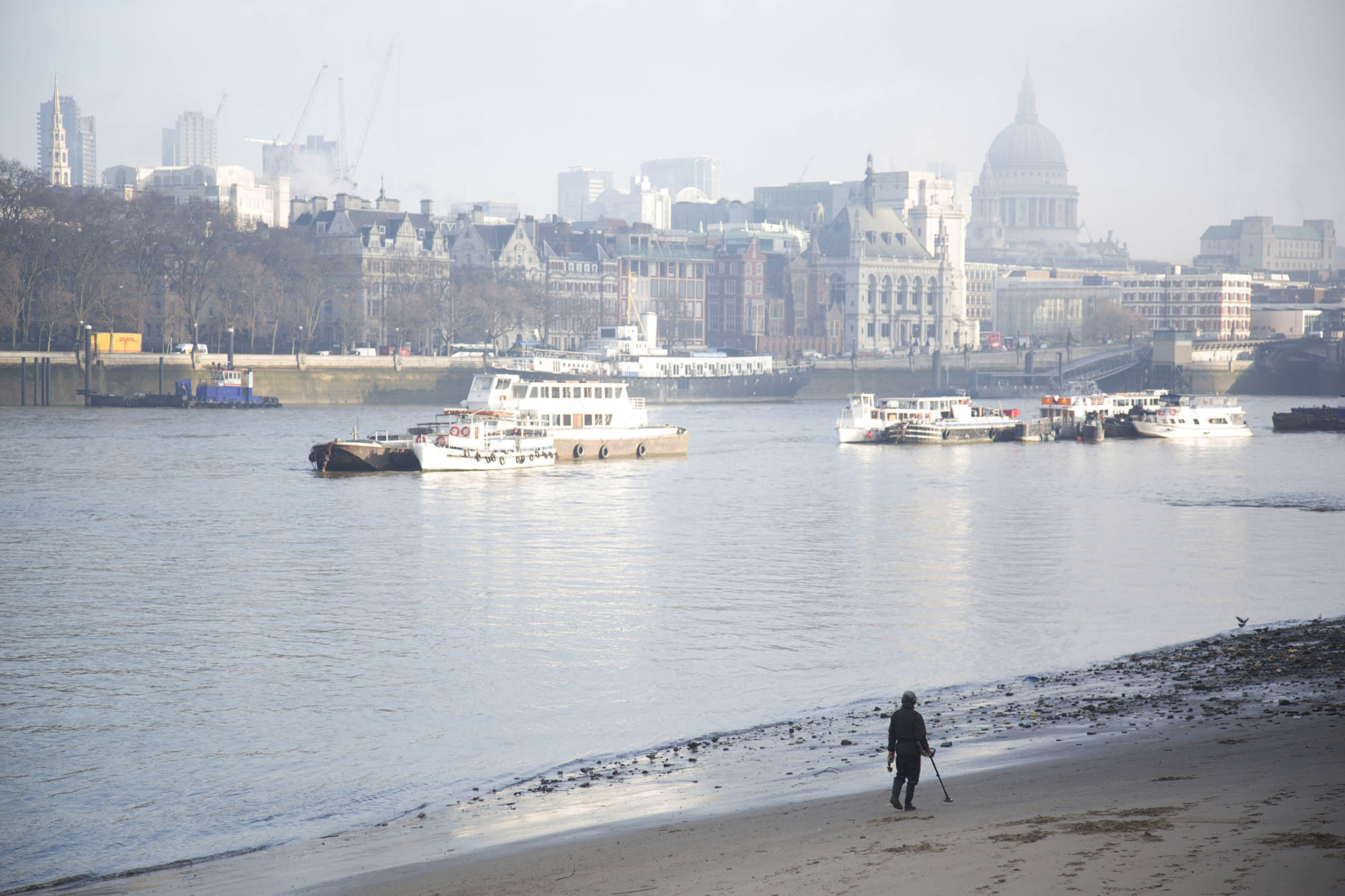 Man walking along the River Thames beach at low tide with his metal detector.