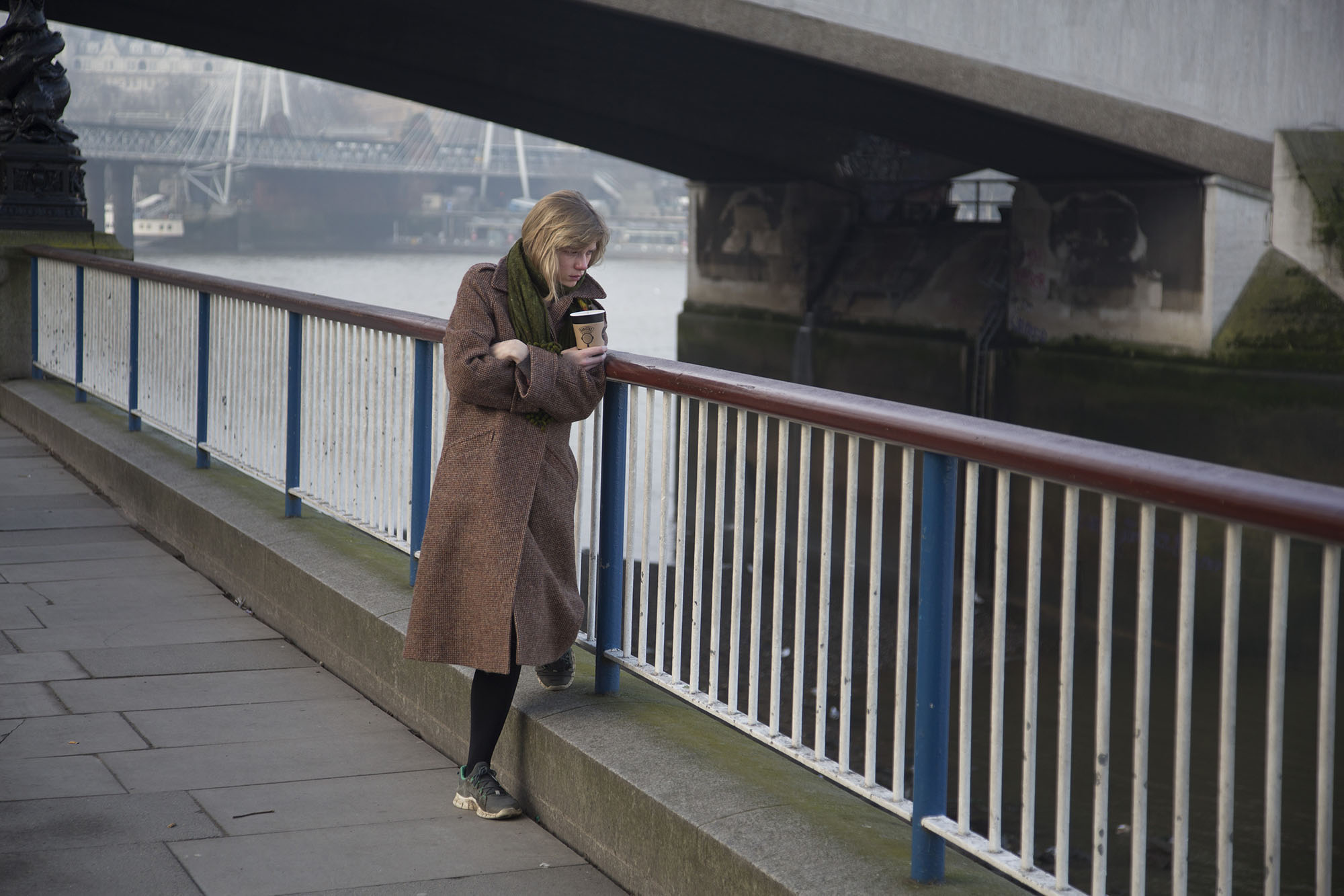 A woman deep in thought looks into the River Thames.