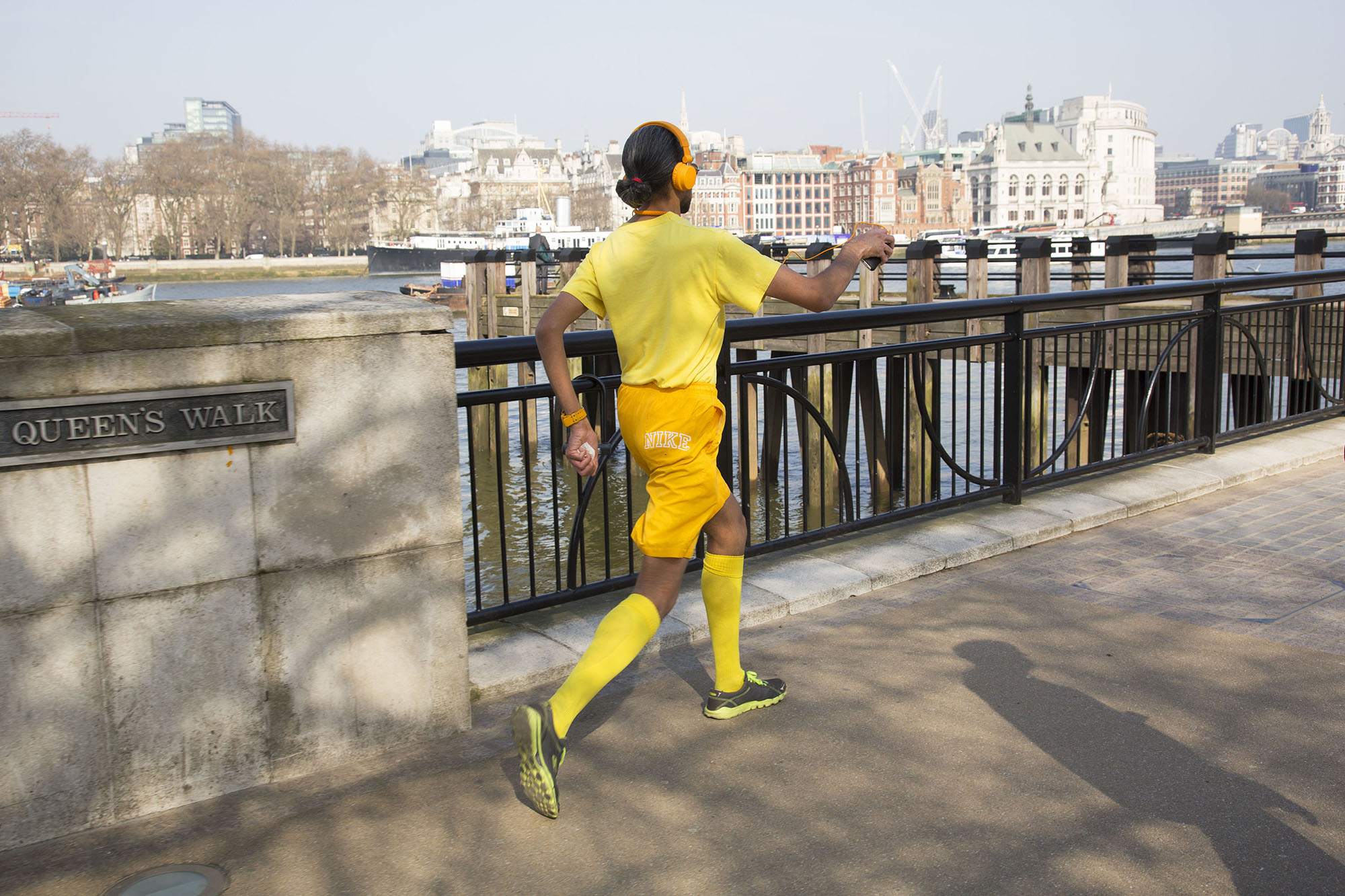Man dressed in yellow, power walking along the Southbank at Queens Walk.