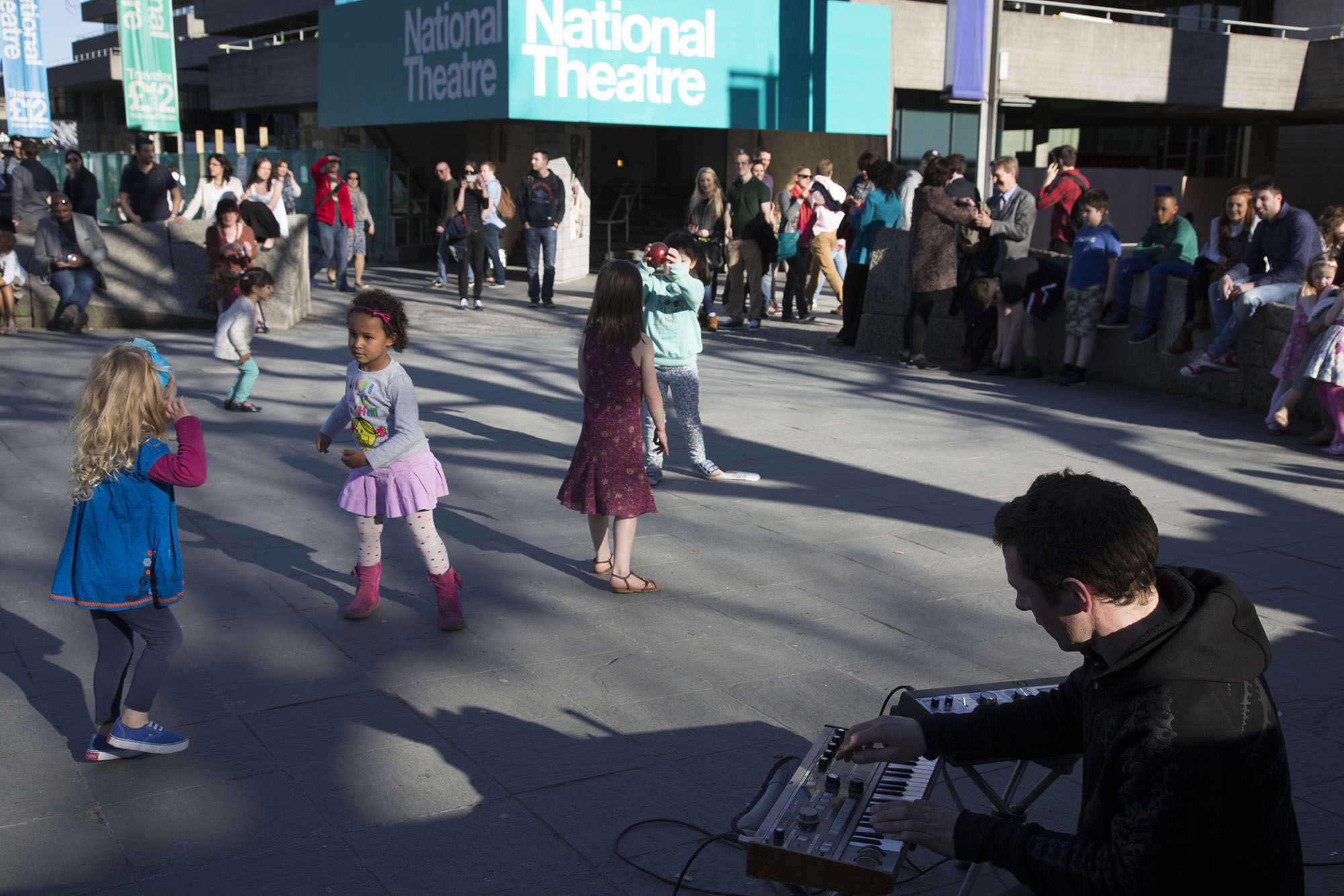 Children spontaneously start to dance to music being made by a busker.