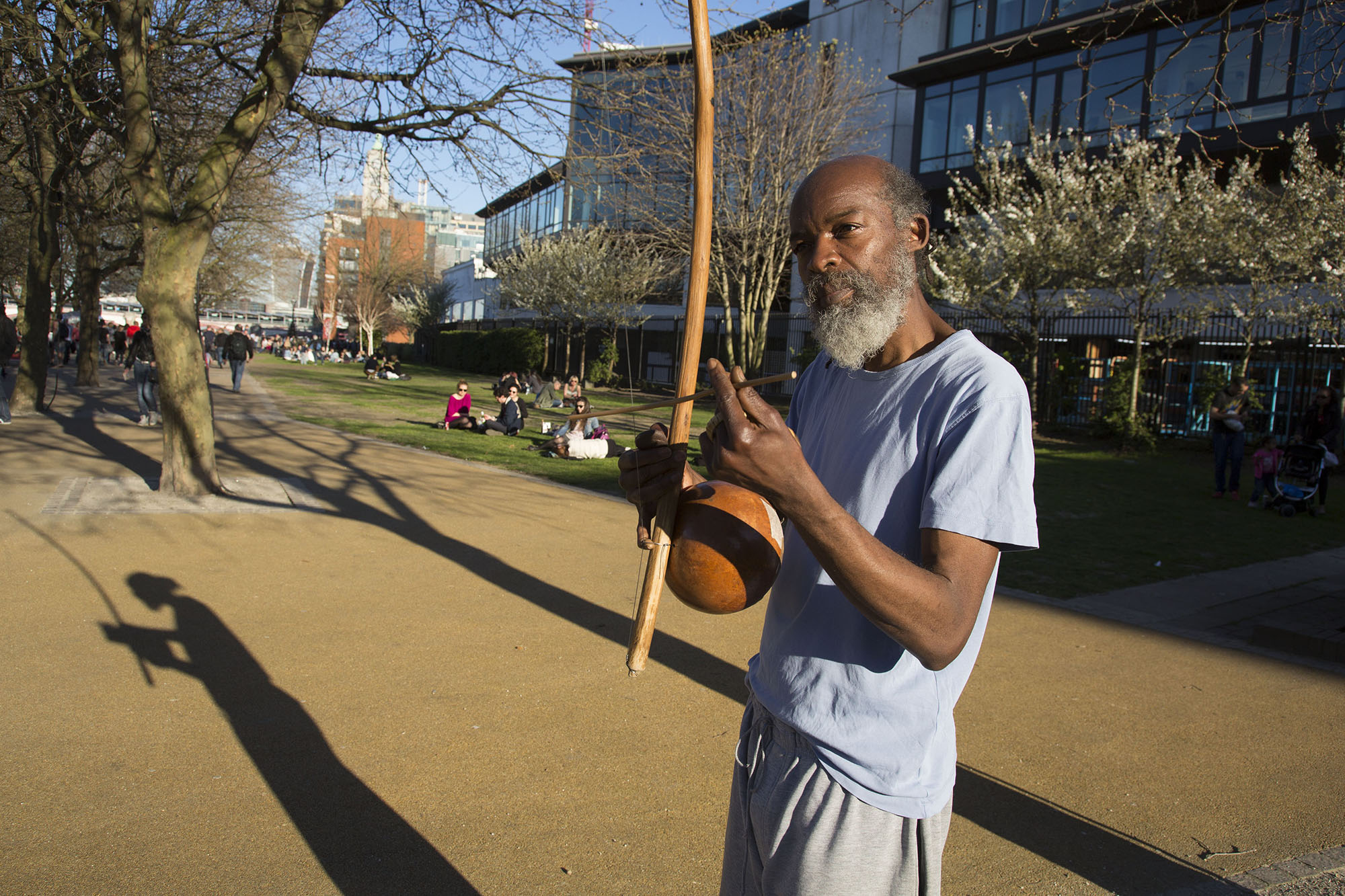 Busker casting his shadow in evening light playing a berimbau.
