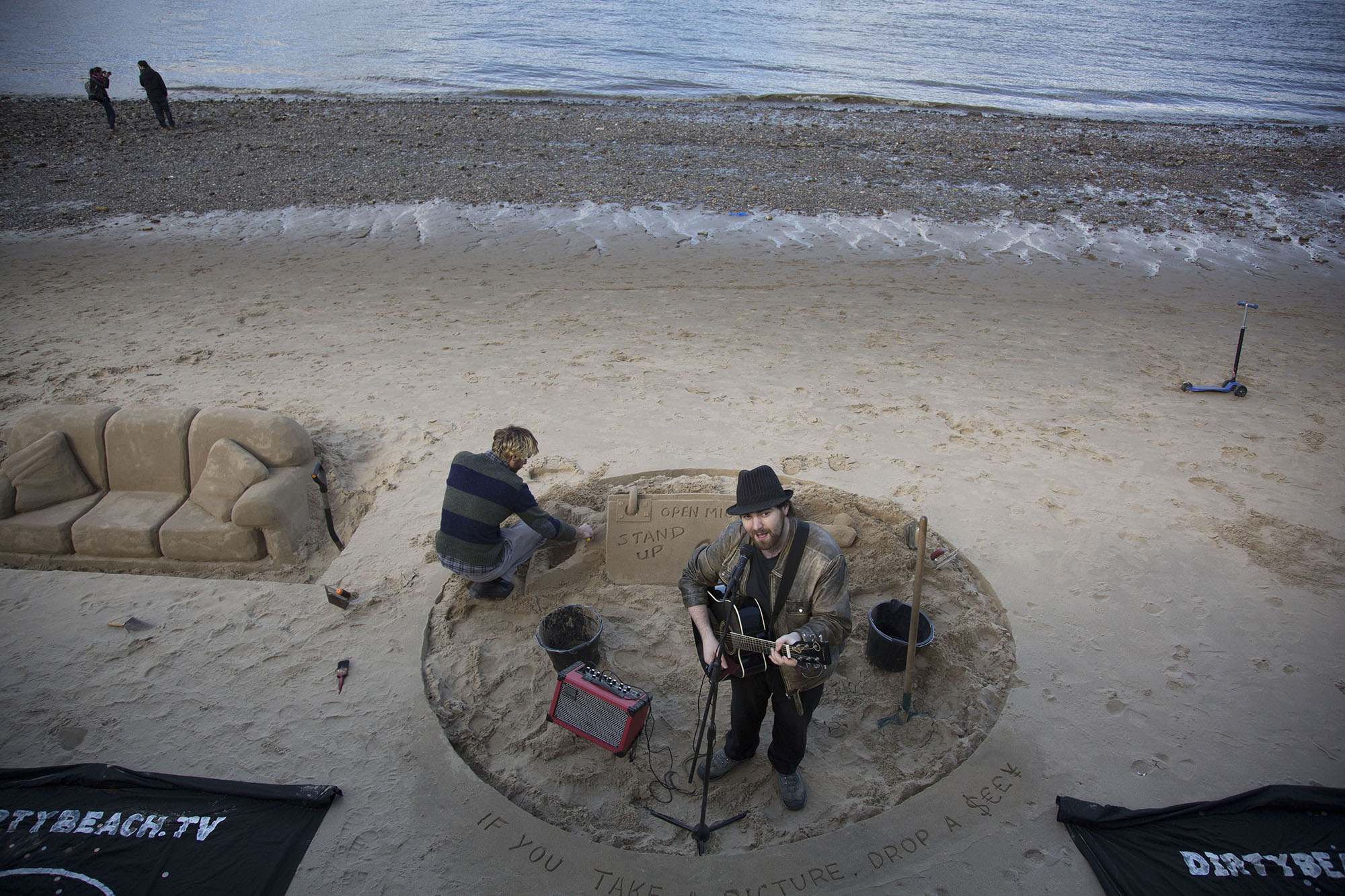 Busker performs amusing songs on the beach of the River Thames.