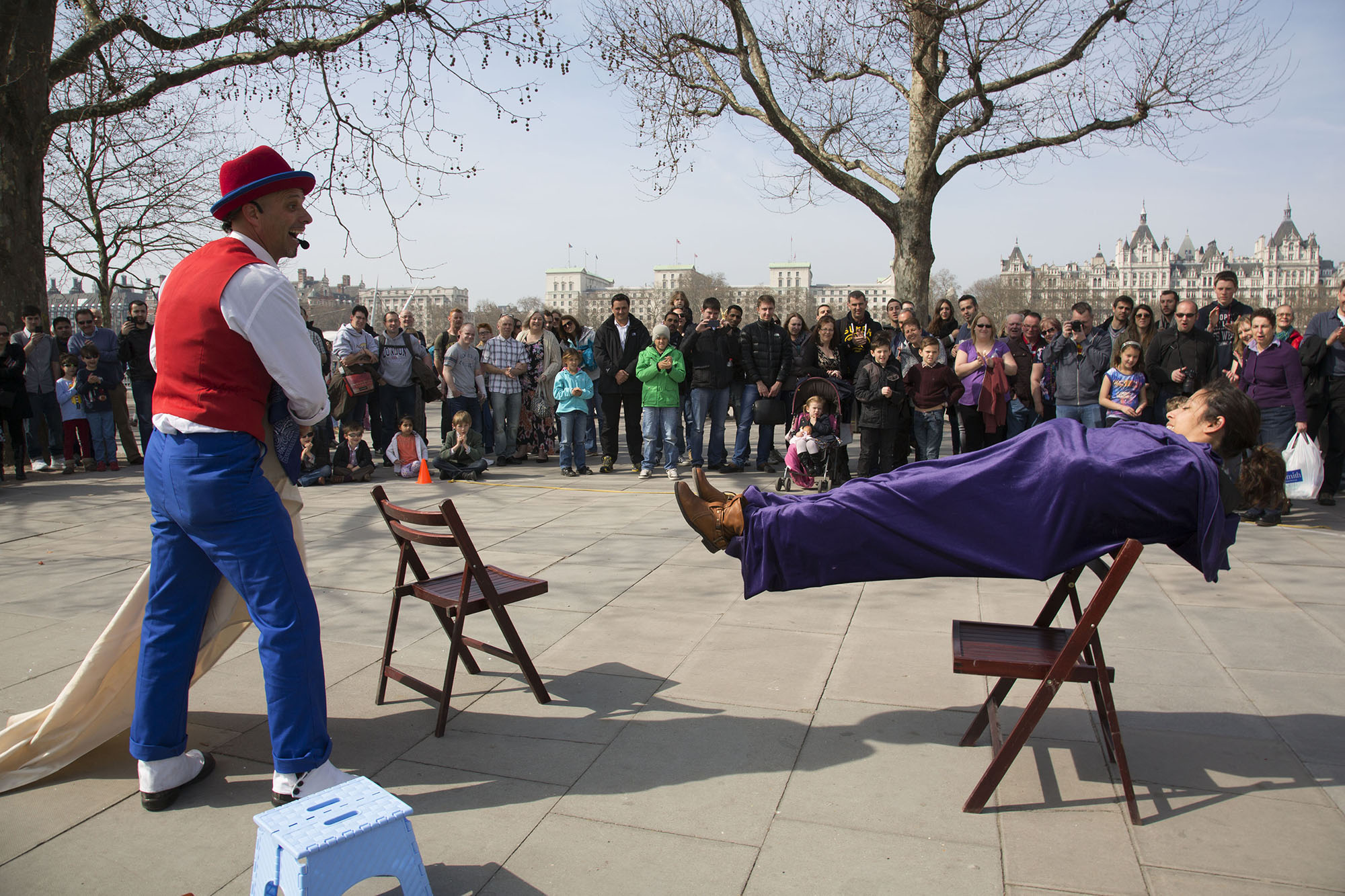 Street performer performs a levitation trick with a member of the public.
