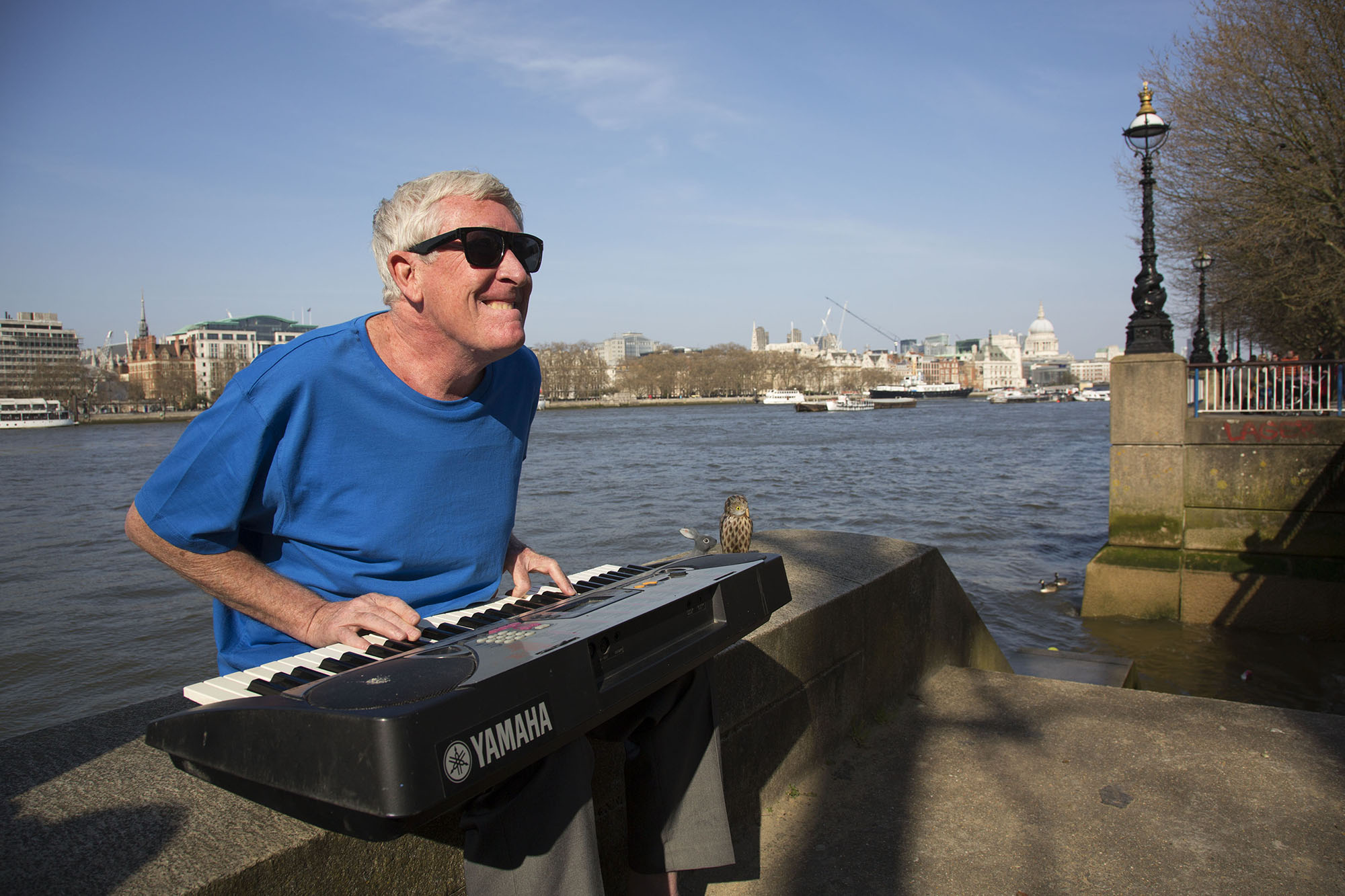 Busking regular playing an electronic organ singing at the riverside.