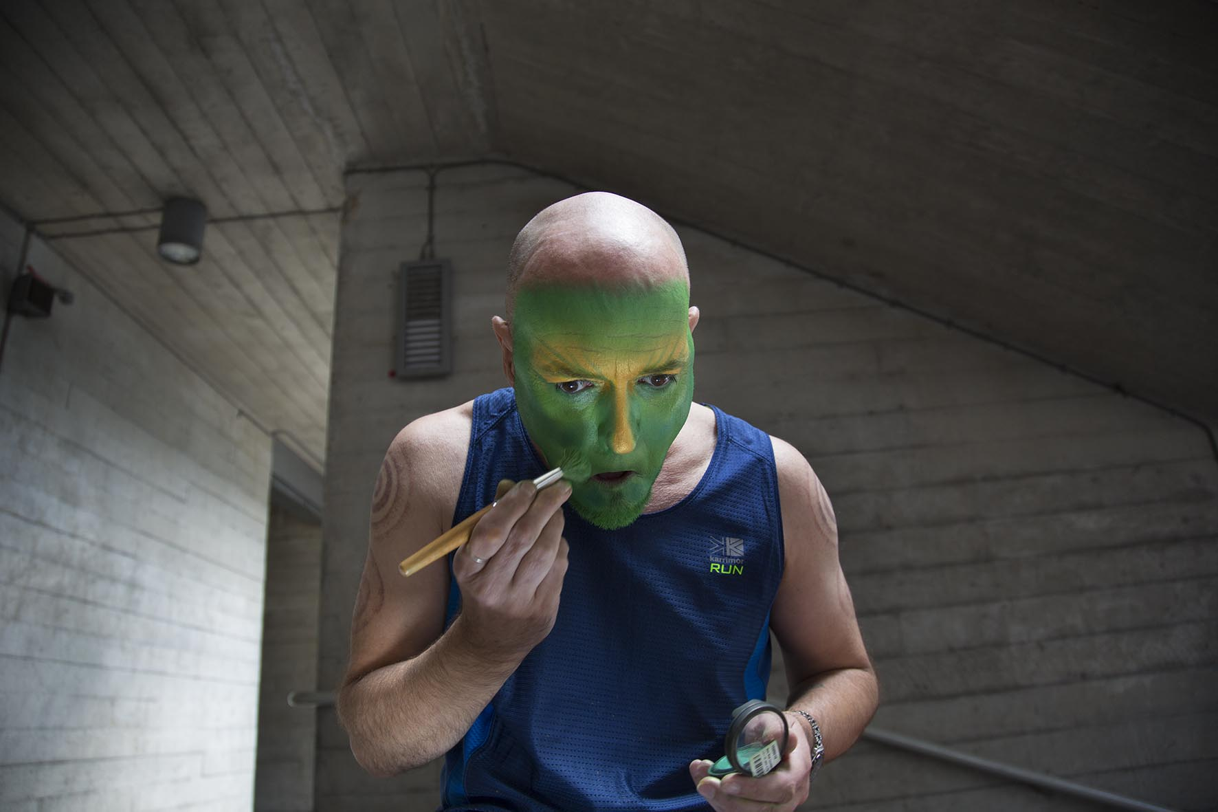 Living statue Mark Tate prepares his make up before a shift as the Green Man in a quiet place under the iconic Southbank concrete architecture.