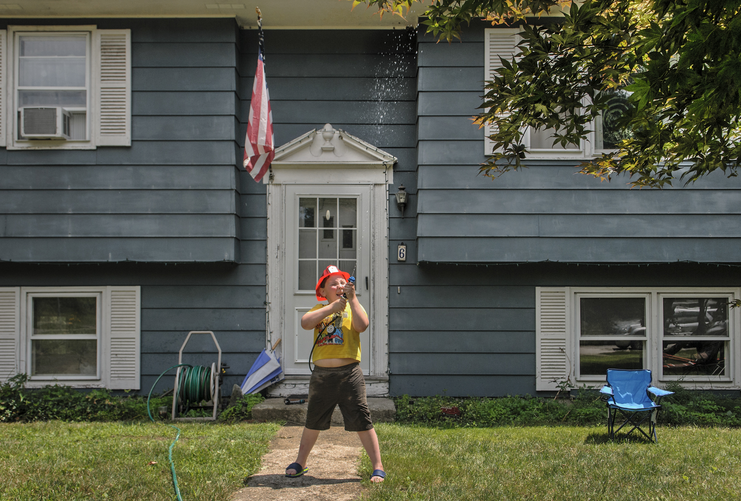 "07.09.2014 - Windham, Ct. - Equipped with a toy fire hose and water-filled canisters strapped to his back, Mason Varga, 6, stands in his front yard spraying water on a pretend fire in his ""climbing tree."" Mason was home with his father, Stephen Varga, a paramedic and Windham Center volunteer firefighter. Mason says that when he grows up he wants to be a Connecticut firefighter for six-months out of the year and a State Trooper in Alaska for the other six. ""They help out their state,"" he explained, ""And in the winter, guess what?...they go out in snowmobiles."""